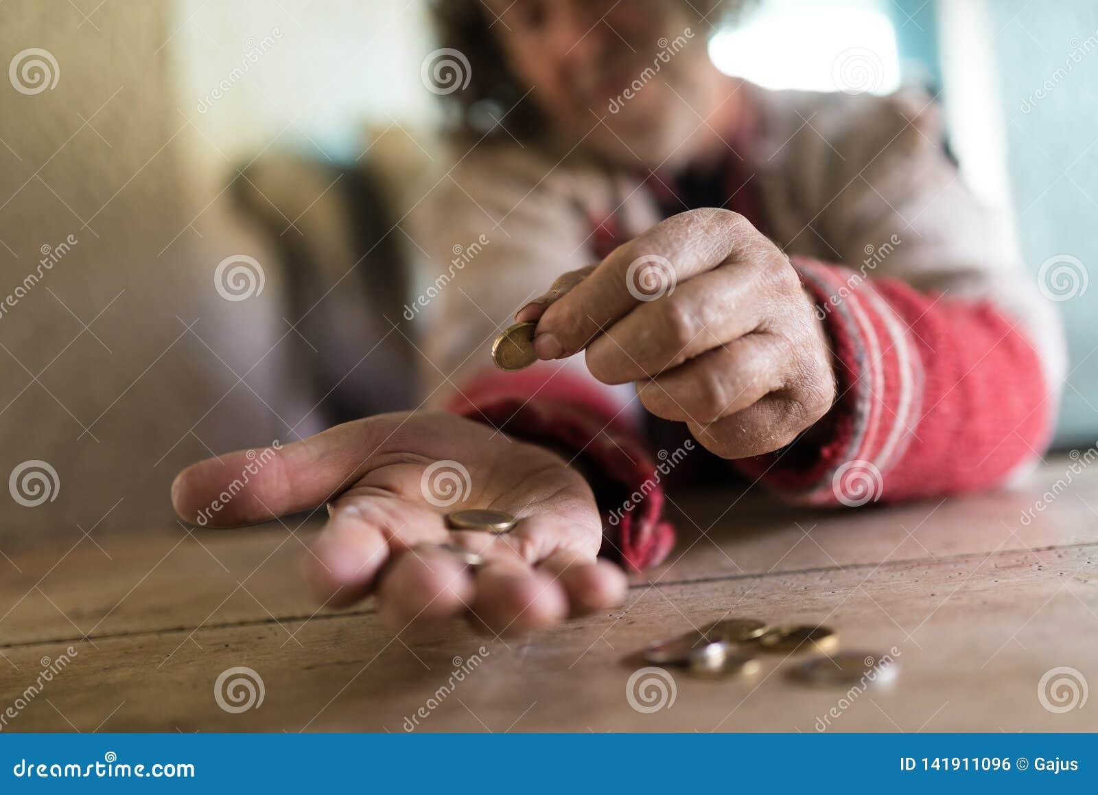 Opinión de ángulo bajo un viejo hombre en el suéter rasgado que cuenta monedas euro