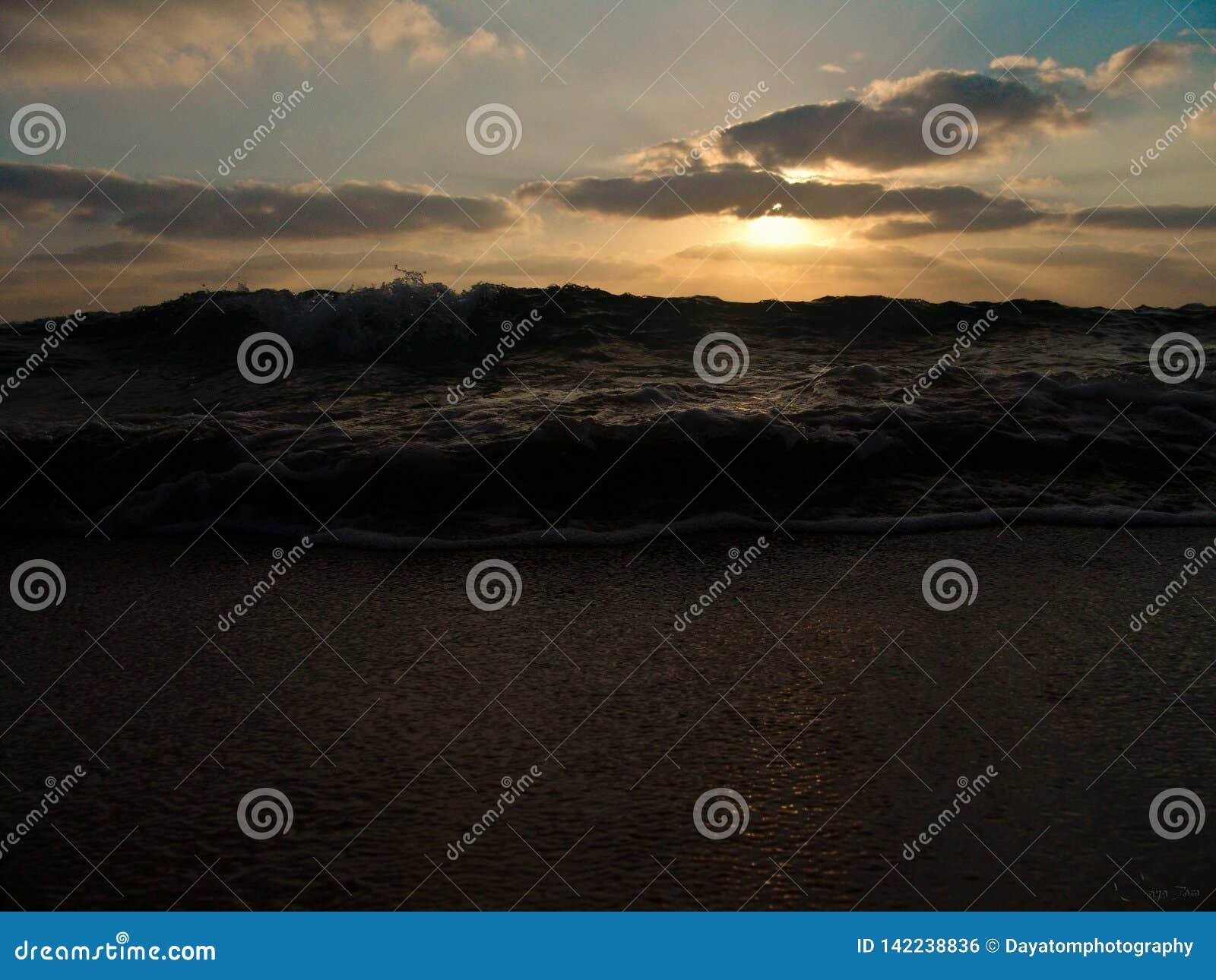 Opinión de ángulo bajo de una onda que salpica en orilla debajo de un cielo nublado en la puesta del sol