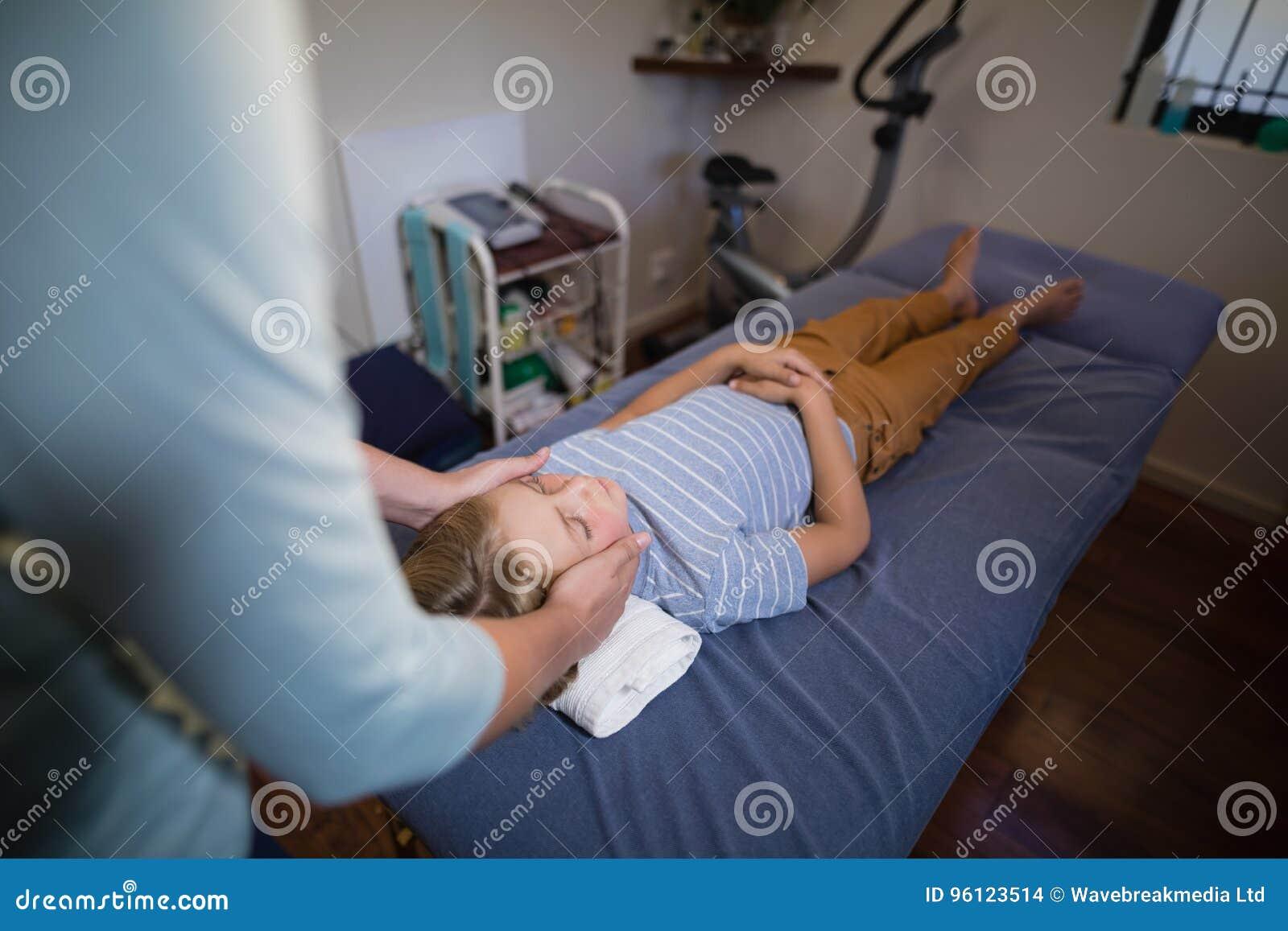 Opinión de alto ángulo el fisioterapeuta de sexo femenino que da el masaje principal al muchacho que miente en cama