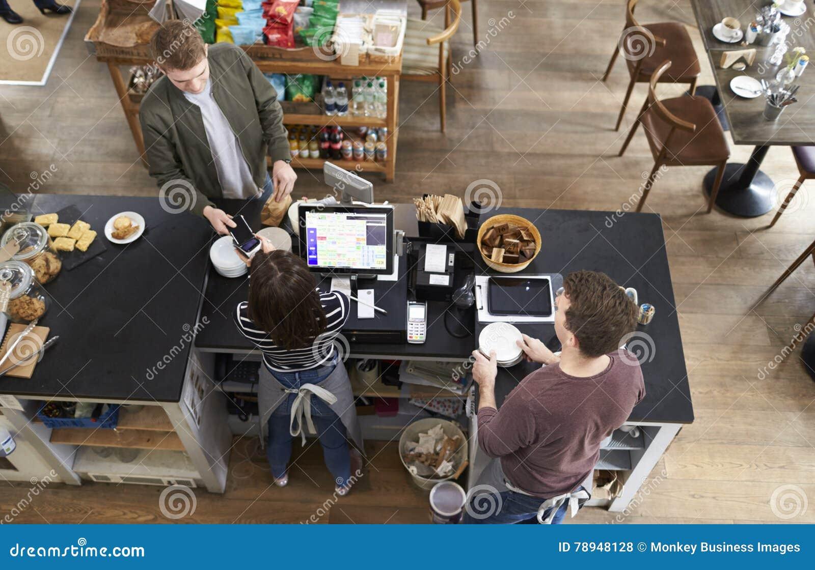 Opinión de alto ángulo el hombre que paga sobre contador en una cafetería