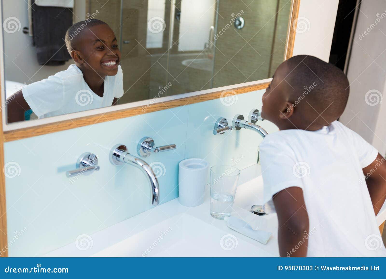 Opinión de alto ángulo el muchacho que aprieta los dientes mientras que mira el espejo