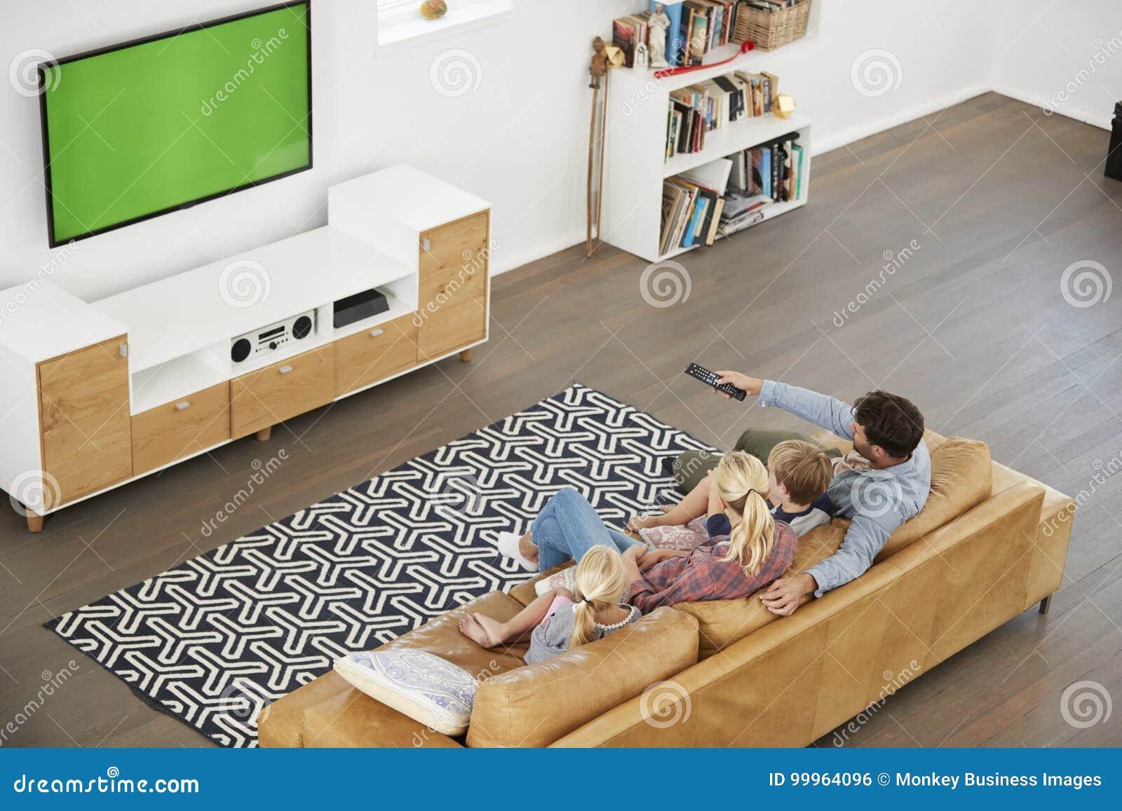 Opinión de alto ángulo la familia que se sienta en Sofa In Lounge Watching TV