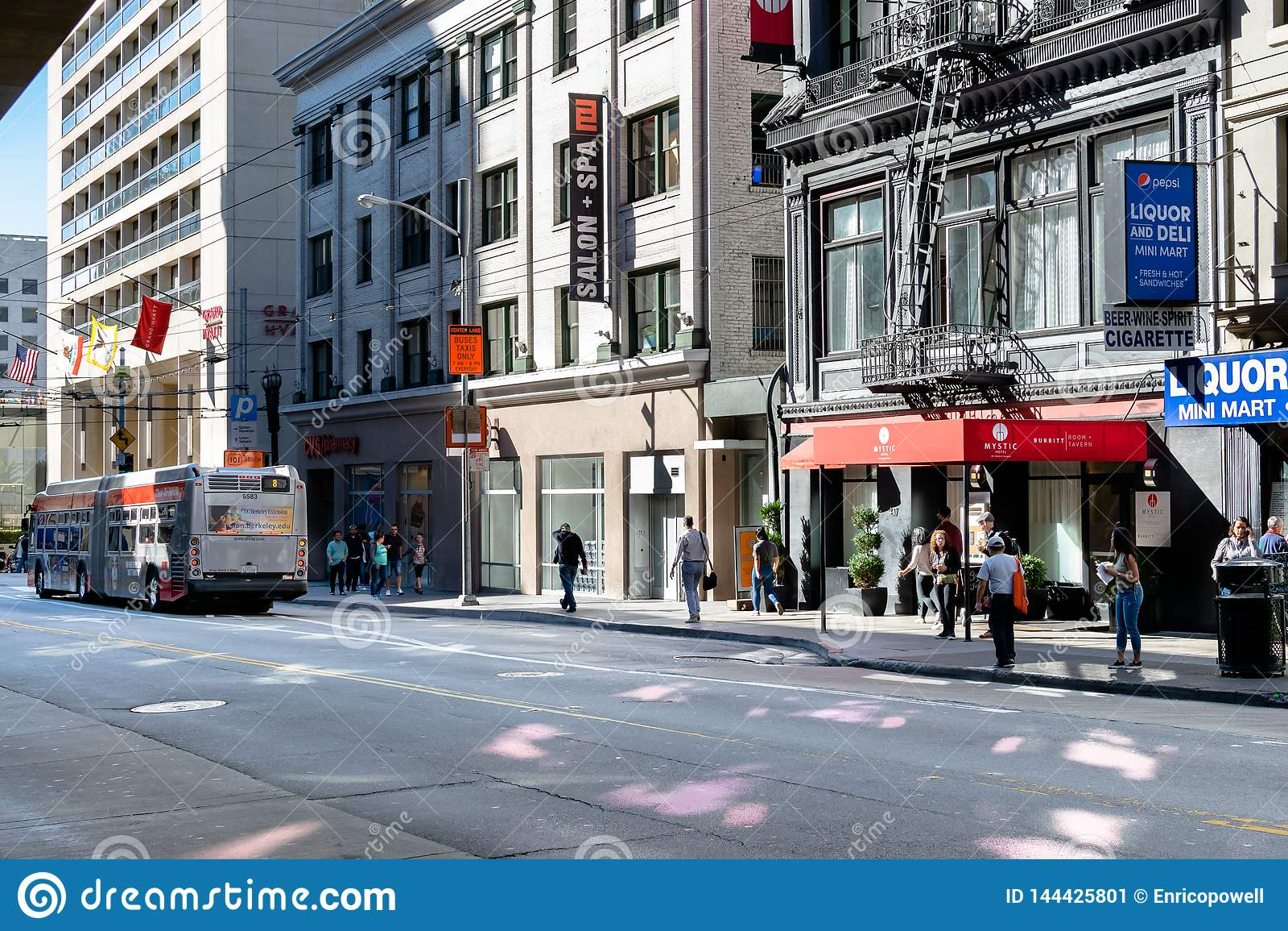 Opinión de la calle en San Francisco de peatones, de tiendas y de un autobús del MTA