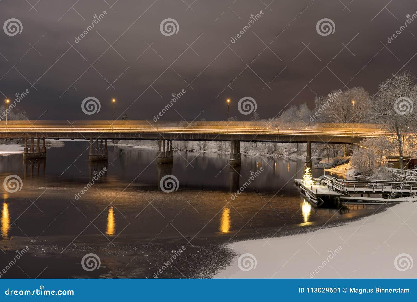 Opinión de la noche del tráfico que cruza un puente concreto a través de un río