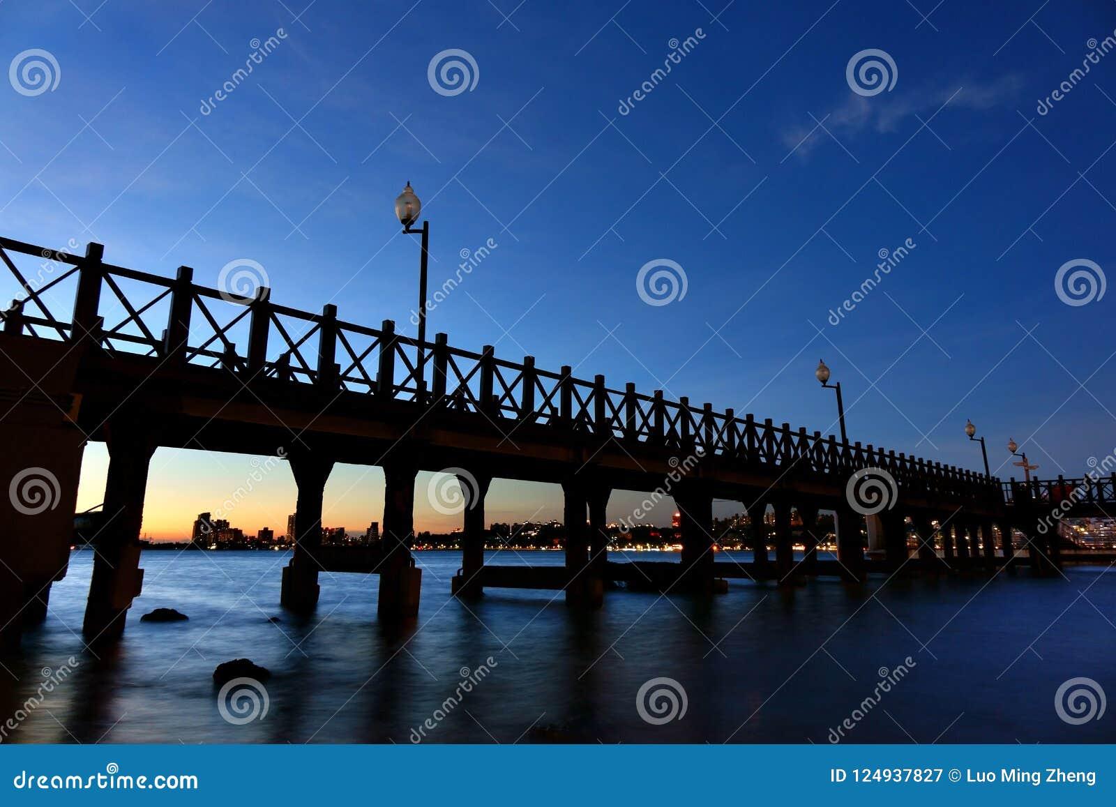 Opinión de la noche de la silueta de madera de la calzada con paisaje urbano en riverbank