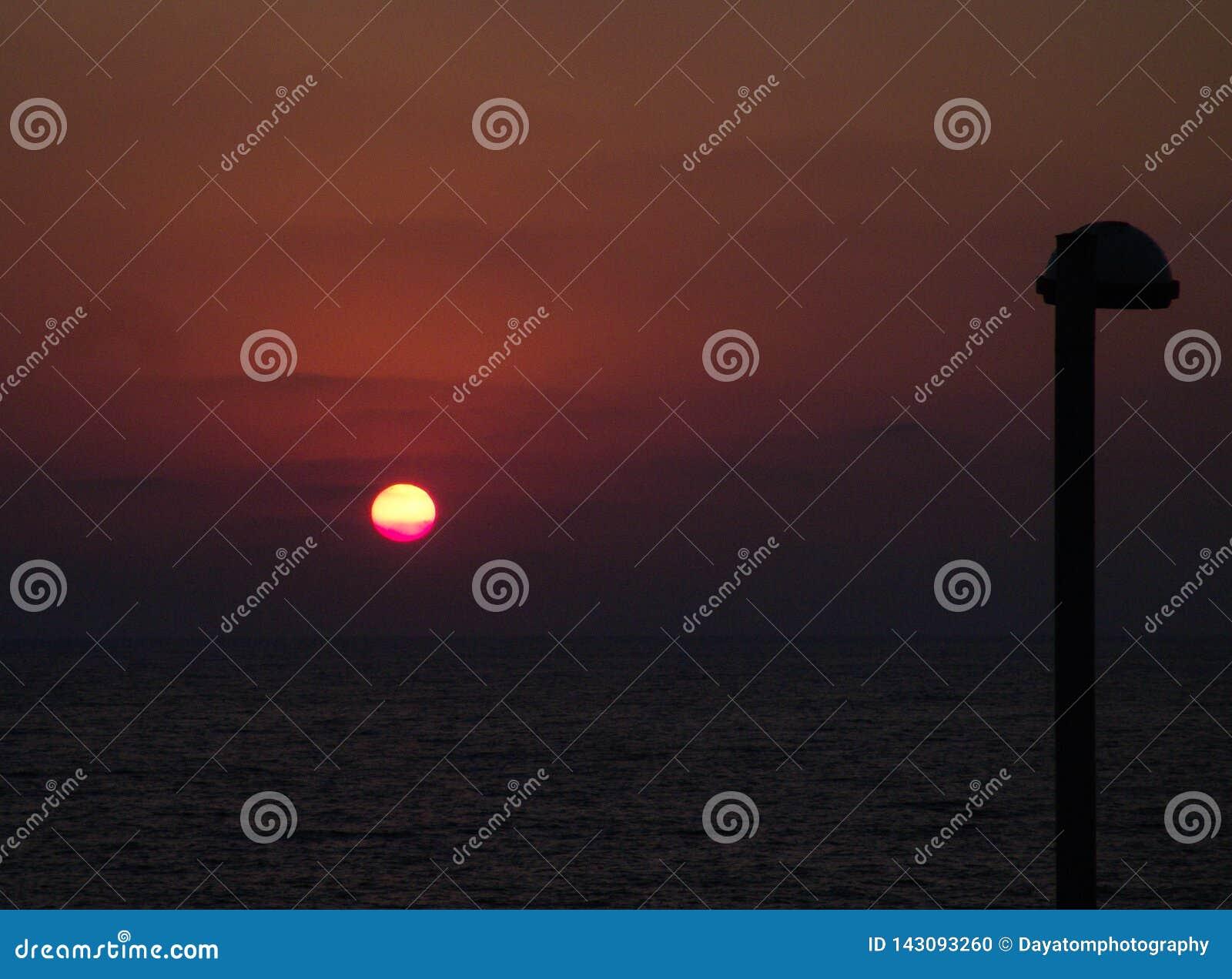 Opinión de la puesta del sol de un parque con las lámparas de la ciudad y la hierba verde en el océano