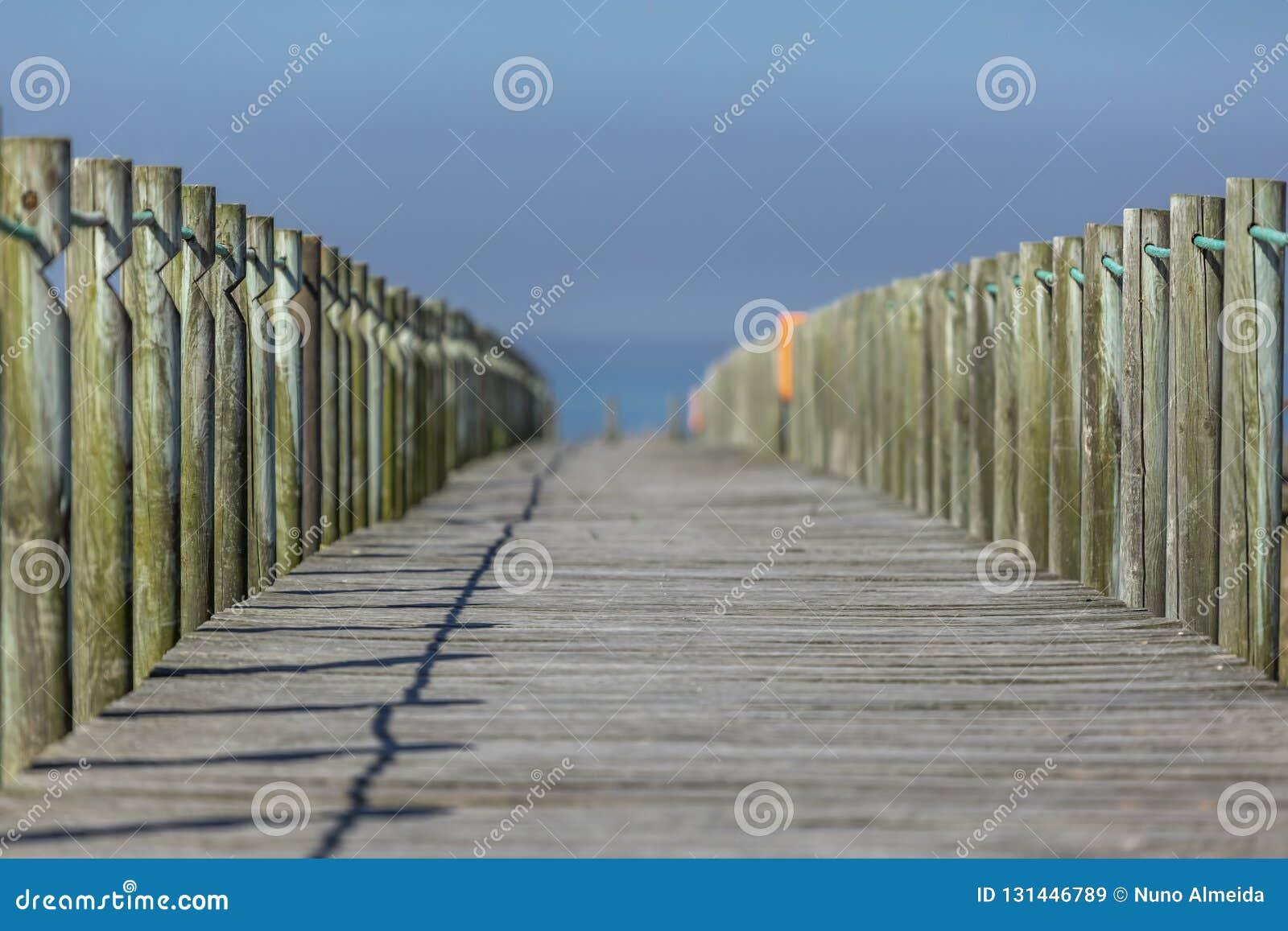 Opinión de perspectiva de la calzada peatonal de madera, hacia el océano, al lado de la playa, Portugal
