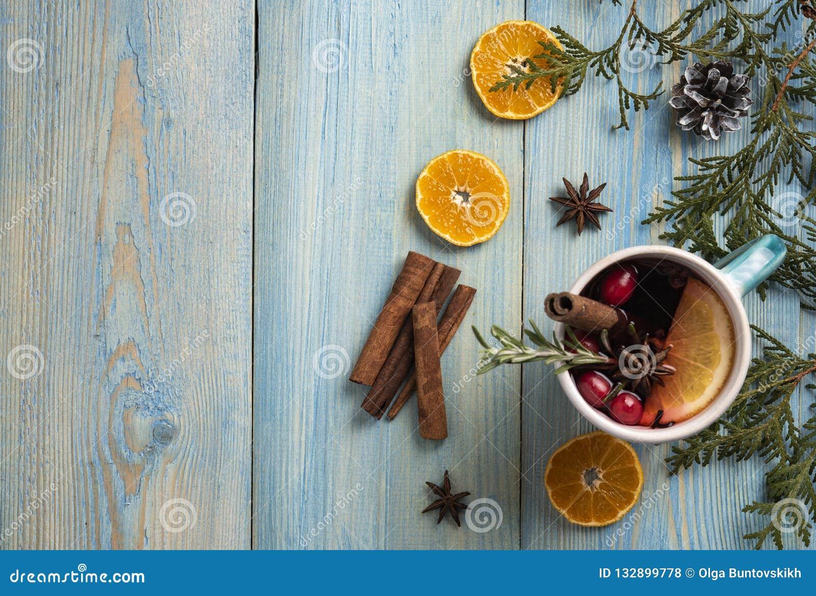 Opinión de top anaranjada del canela del fondo azul de la Navidad del vino tinto