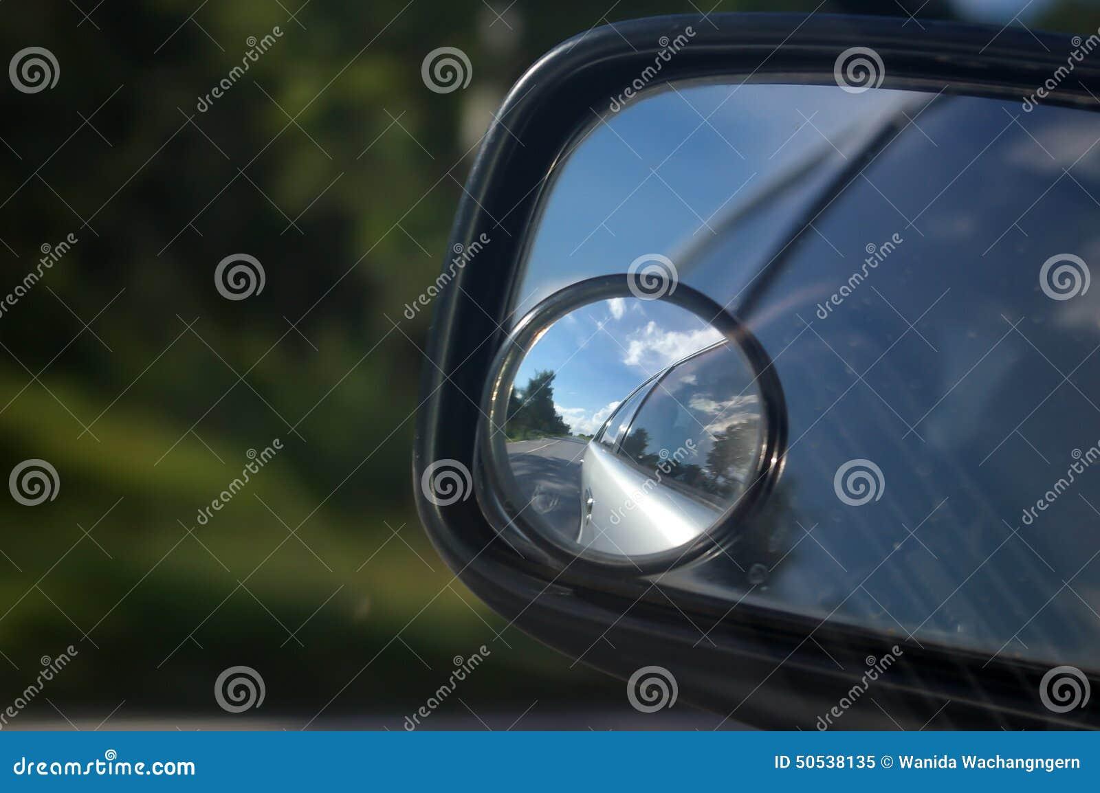 Opinión del camino en una reflexión de espejo de coche