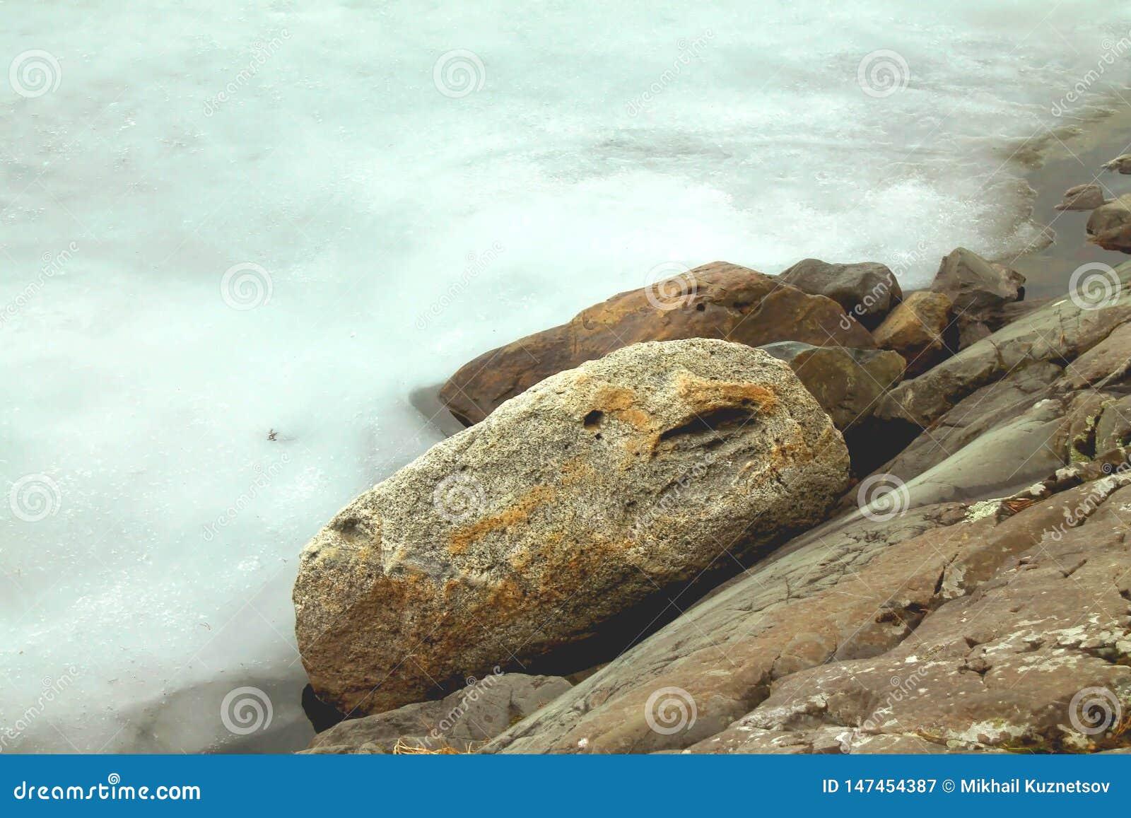 Opinión del invierno al hielo y a las rocas nevosos en las orillas del lago helado