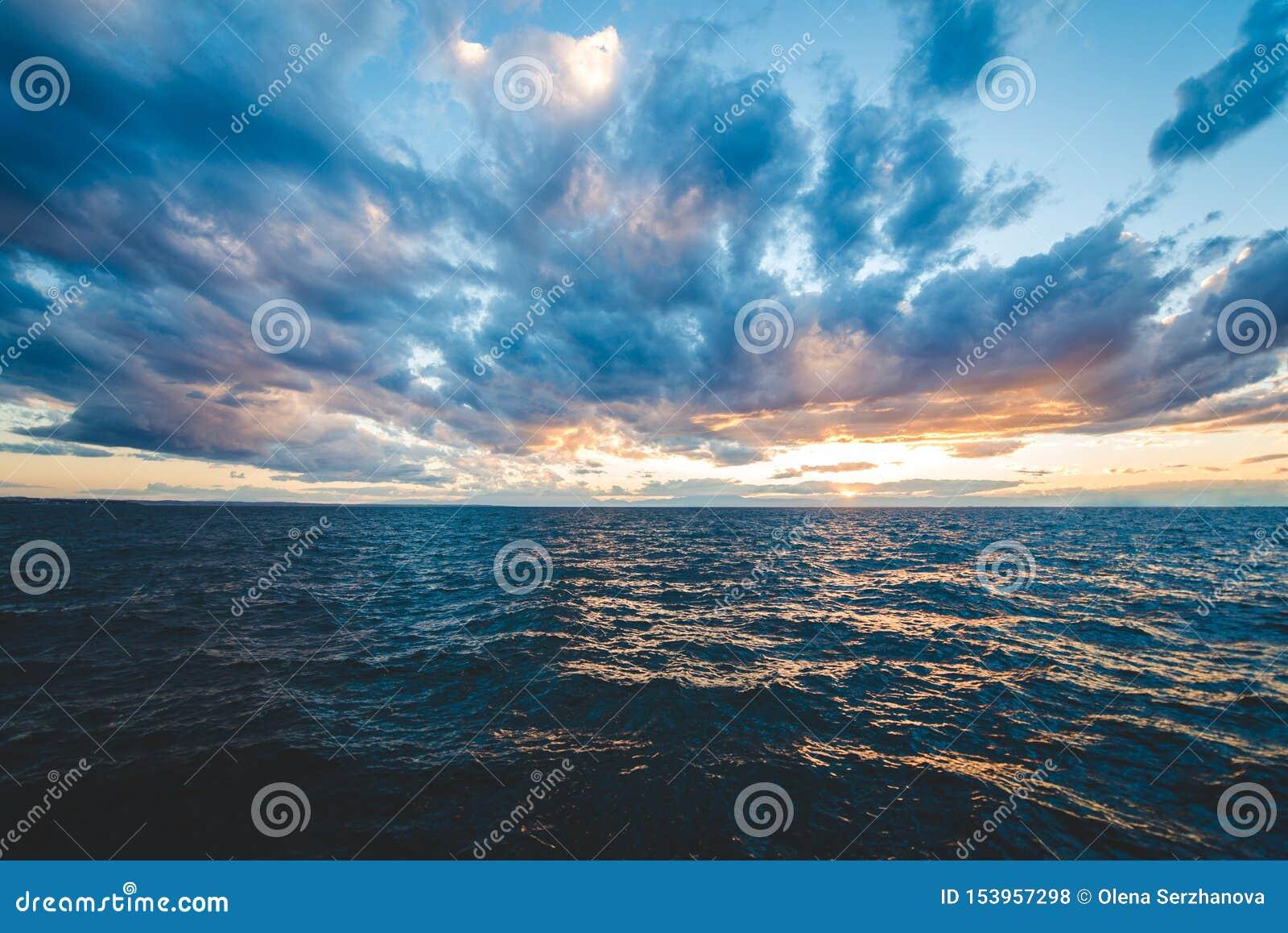 Opinión del mar de la puesta del sol con el cielo dramático y las nubes coloridas
