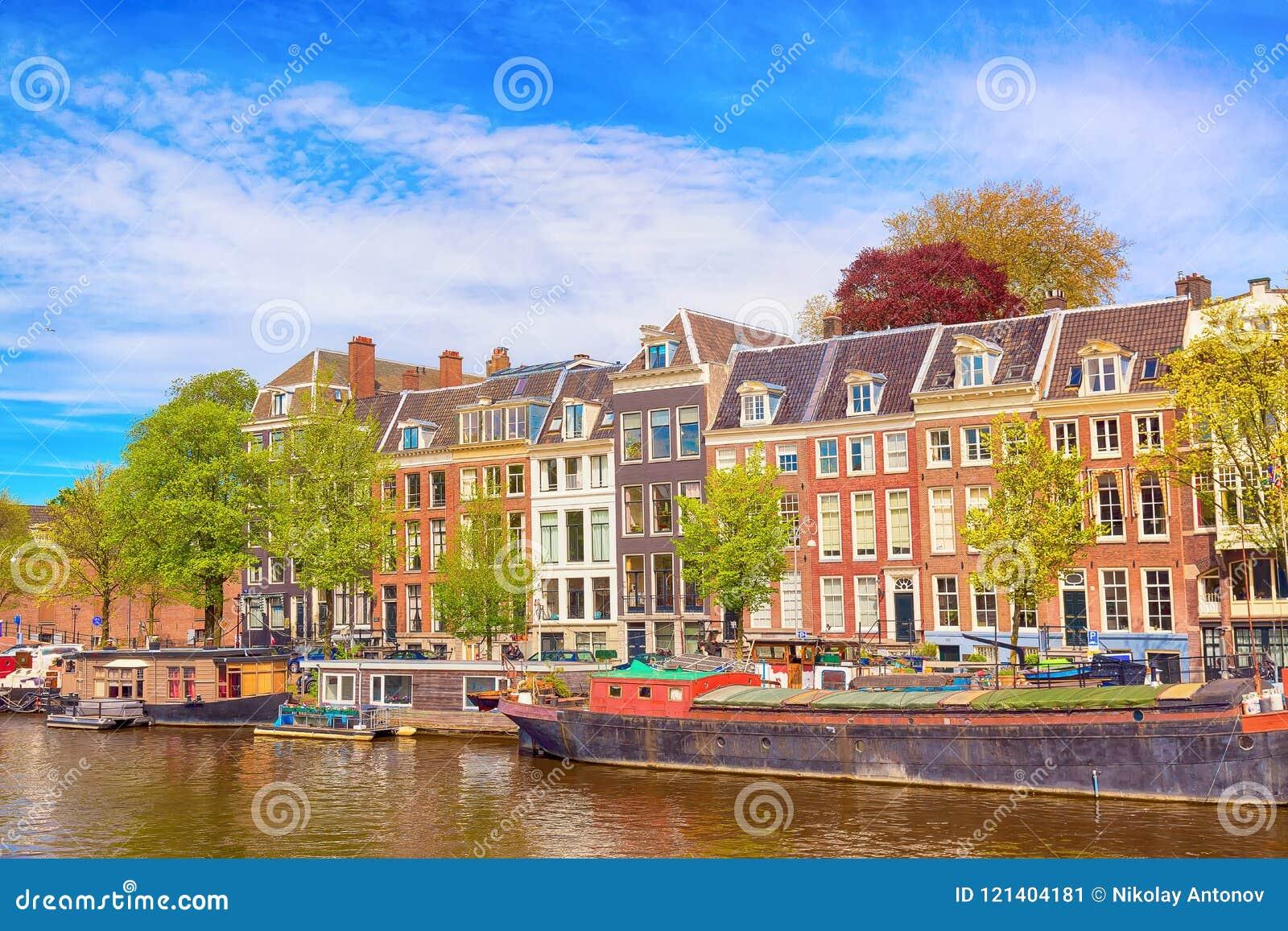 Opinión del paisaje urbano del canal de Amsterdam en verano con un cielo azul, barcos de casa y casas viejas tradicionales Pintor