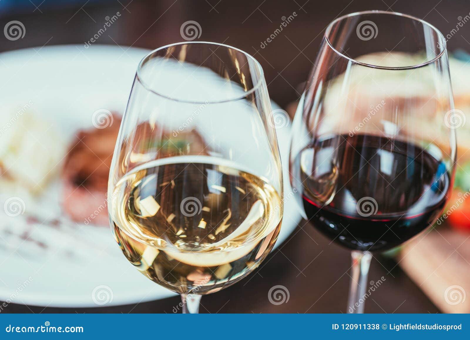 Opinión del primer de dos vidrios con el vino blanco rojo y en la tabla