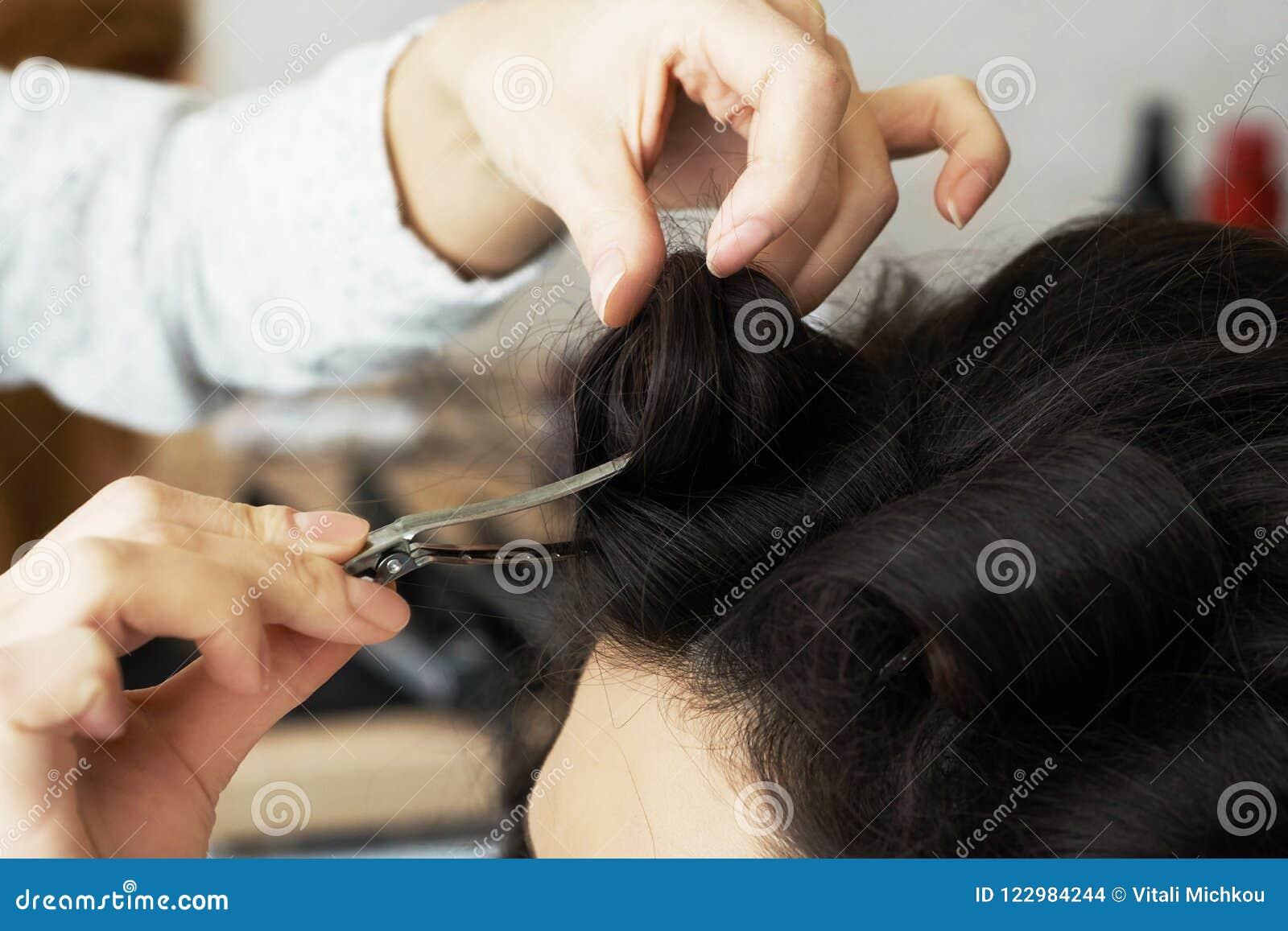 Opinión del primer de la mano del peluquero que peina un nuevo peinado en una cabeza del cliente en salón de pelo