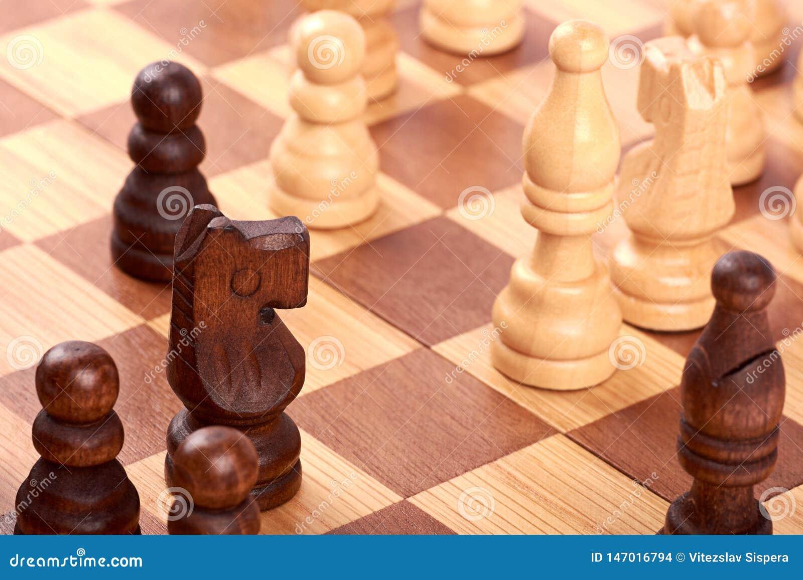 Opinión del primer del juego de ajedrez con los pedazos blancos y negros del registro en el tablero de ajedrez marrón Lucha con e