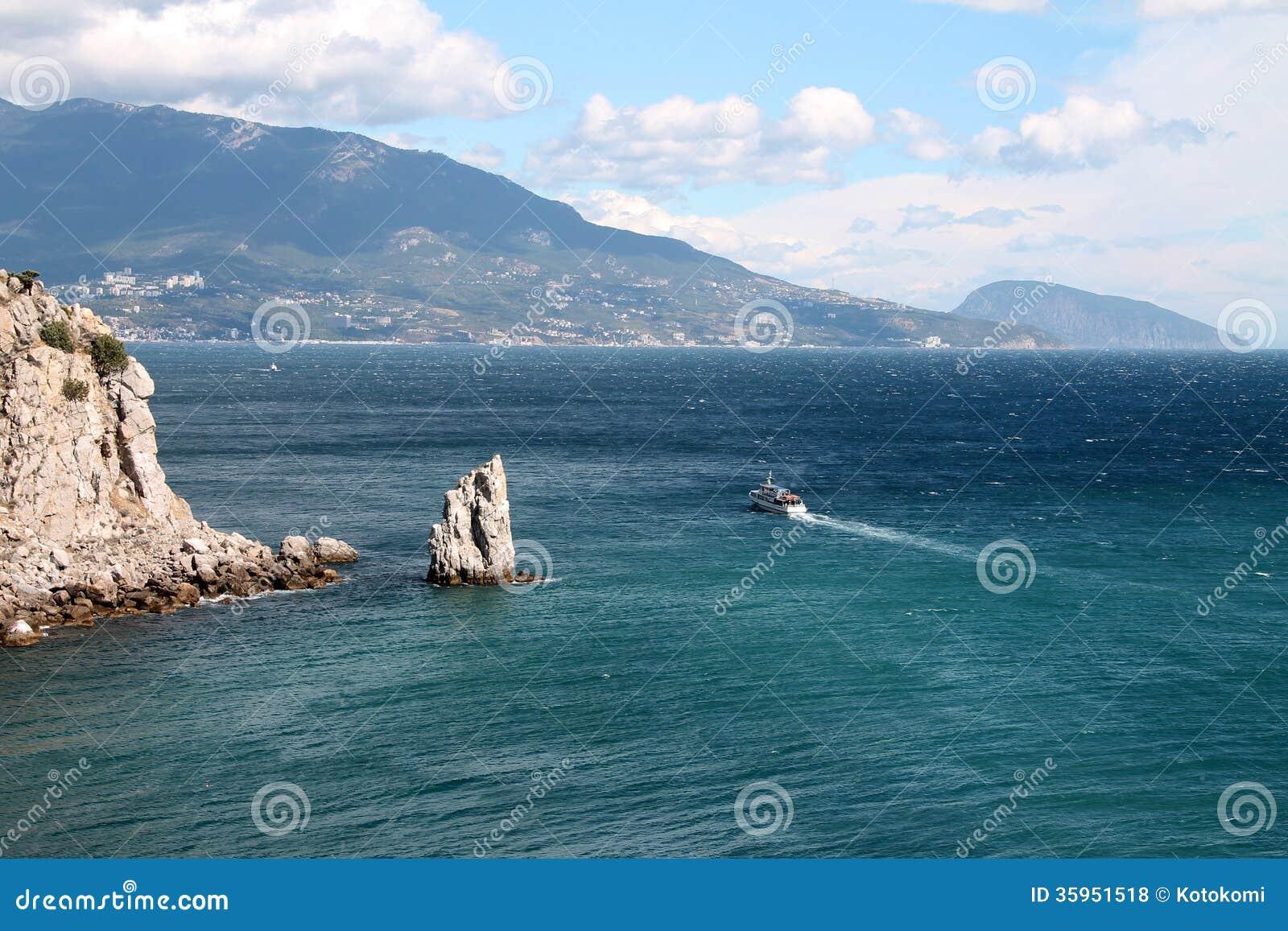 Opinión escénica del mar con las rocas y los acantilados. La nave navega lejos.