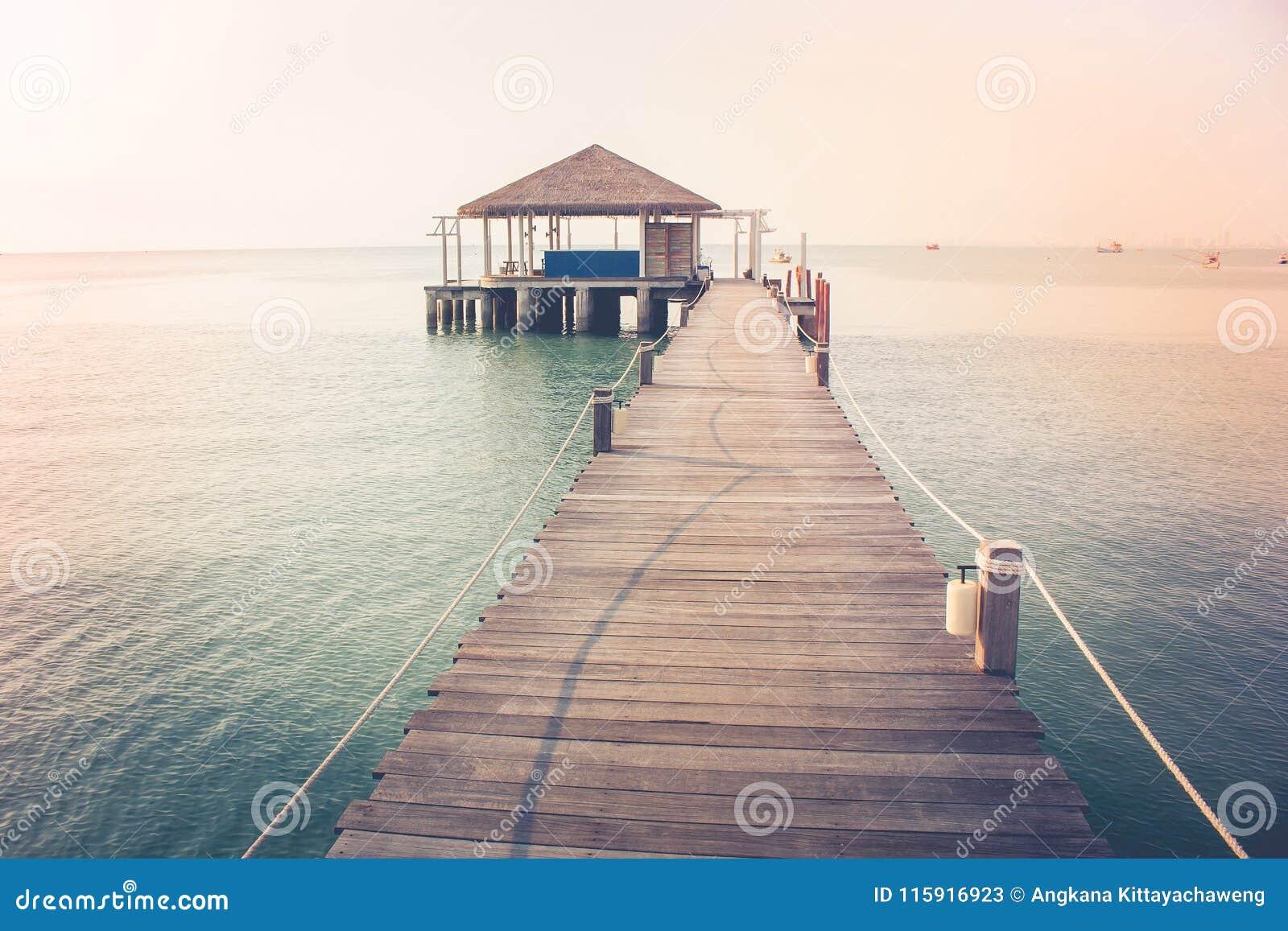 Opinión hermosa del paisaje del puente de madera largo en el mar y el pabellón