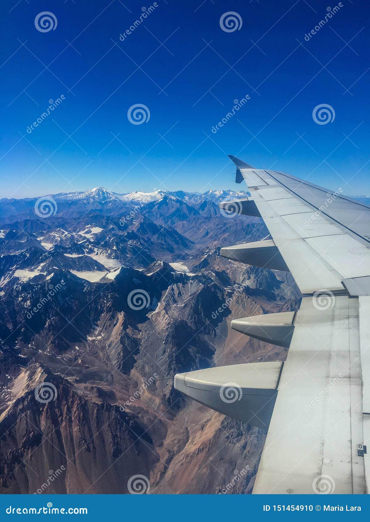 Opinión nevada de la ventana del aeroplano de la montaña