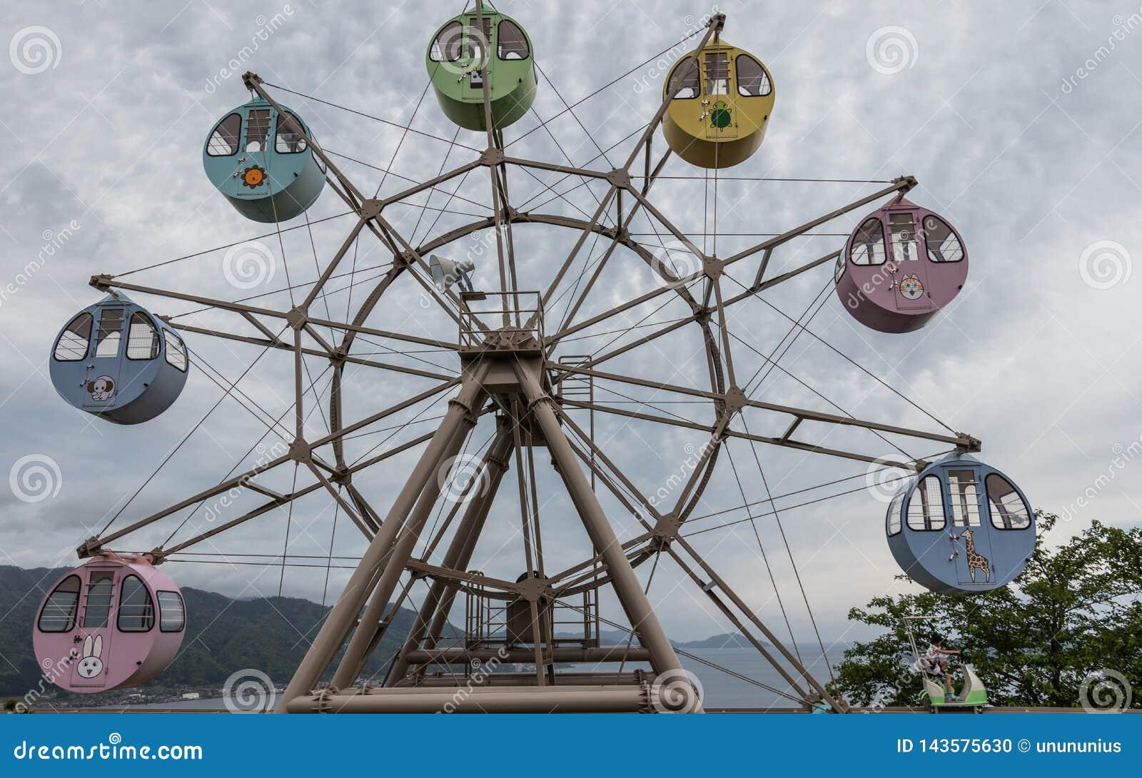Opinión panorámica sobre gran Ferris Wheel con la ronda, cabinas coloridas con los animales impresos Localizado en tierra de la o