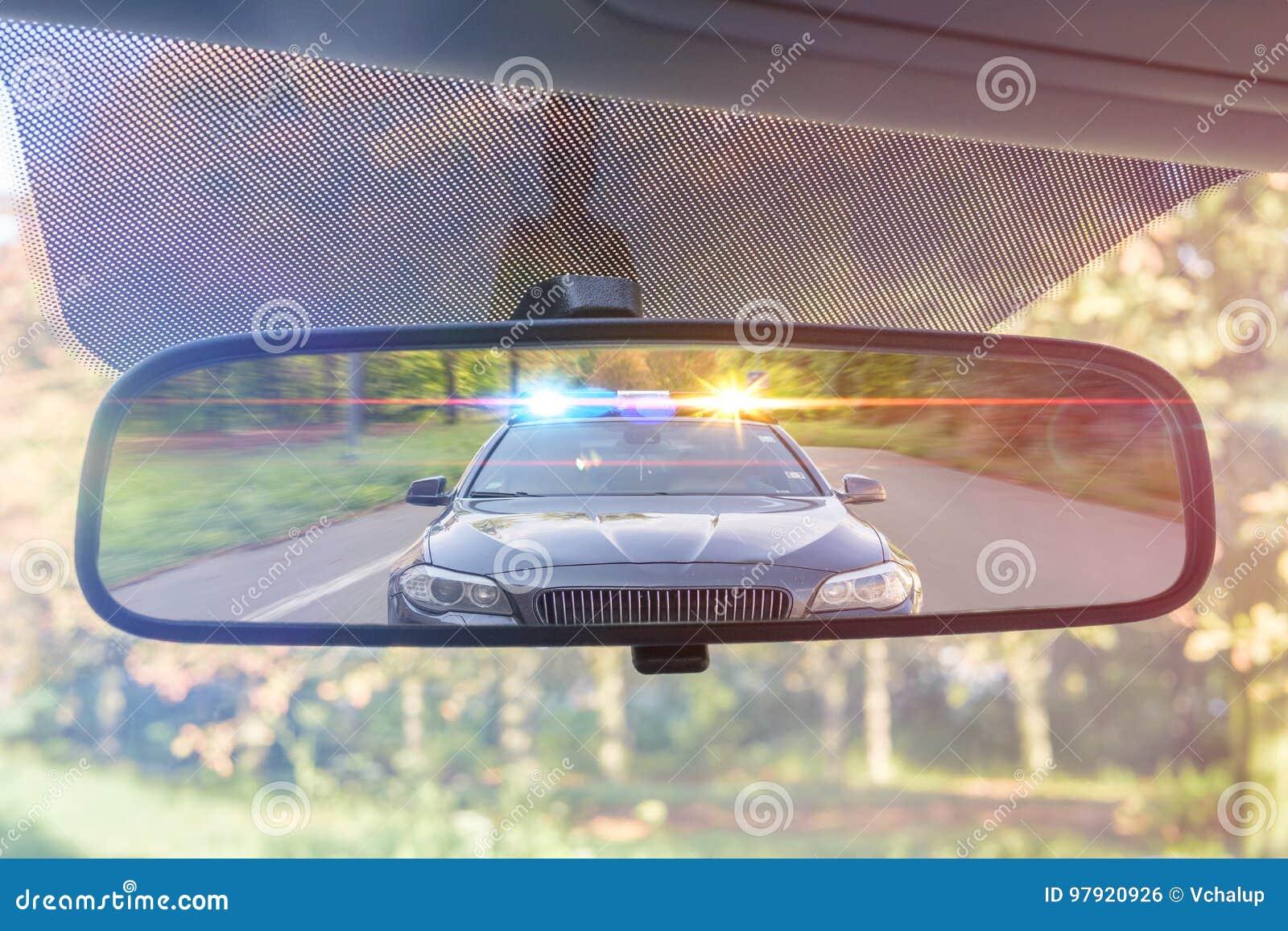 Opinión sobre el espejo posterior de un coche El coche policía con las luces y la sirena le está persiguiendo