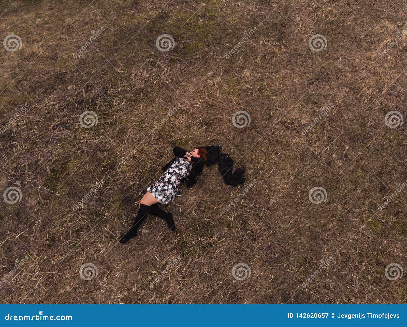 Opinión superior del abejón aéreo una muchacha que miente en un campo que se relaja y que baila Llevar un vestido con las medias