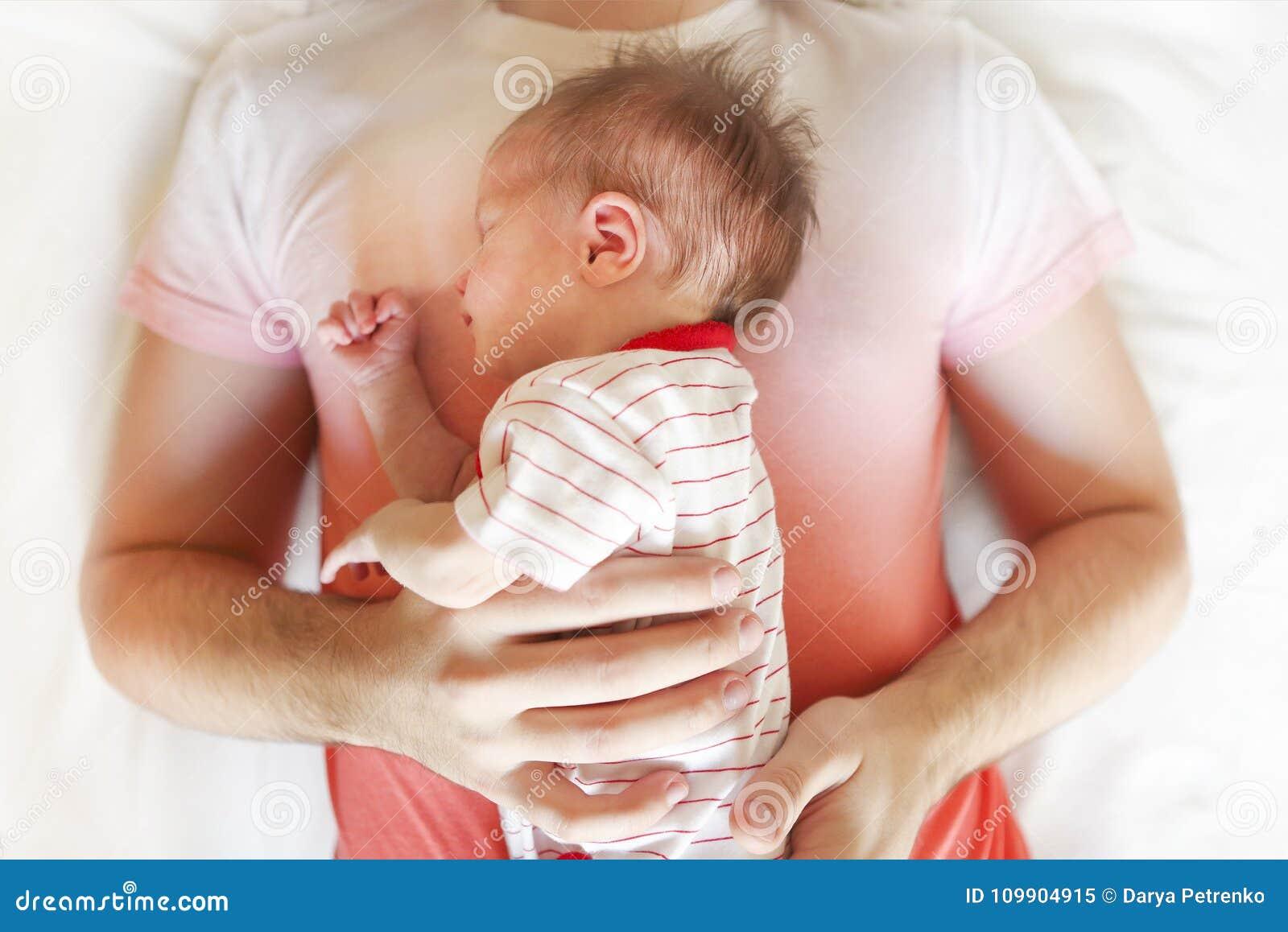 Opinión superior el padre que duerme en cama con la hija recién nacida del bebé
