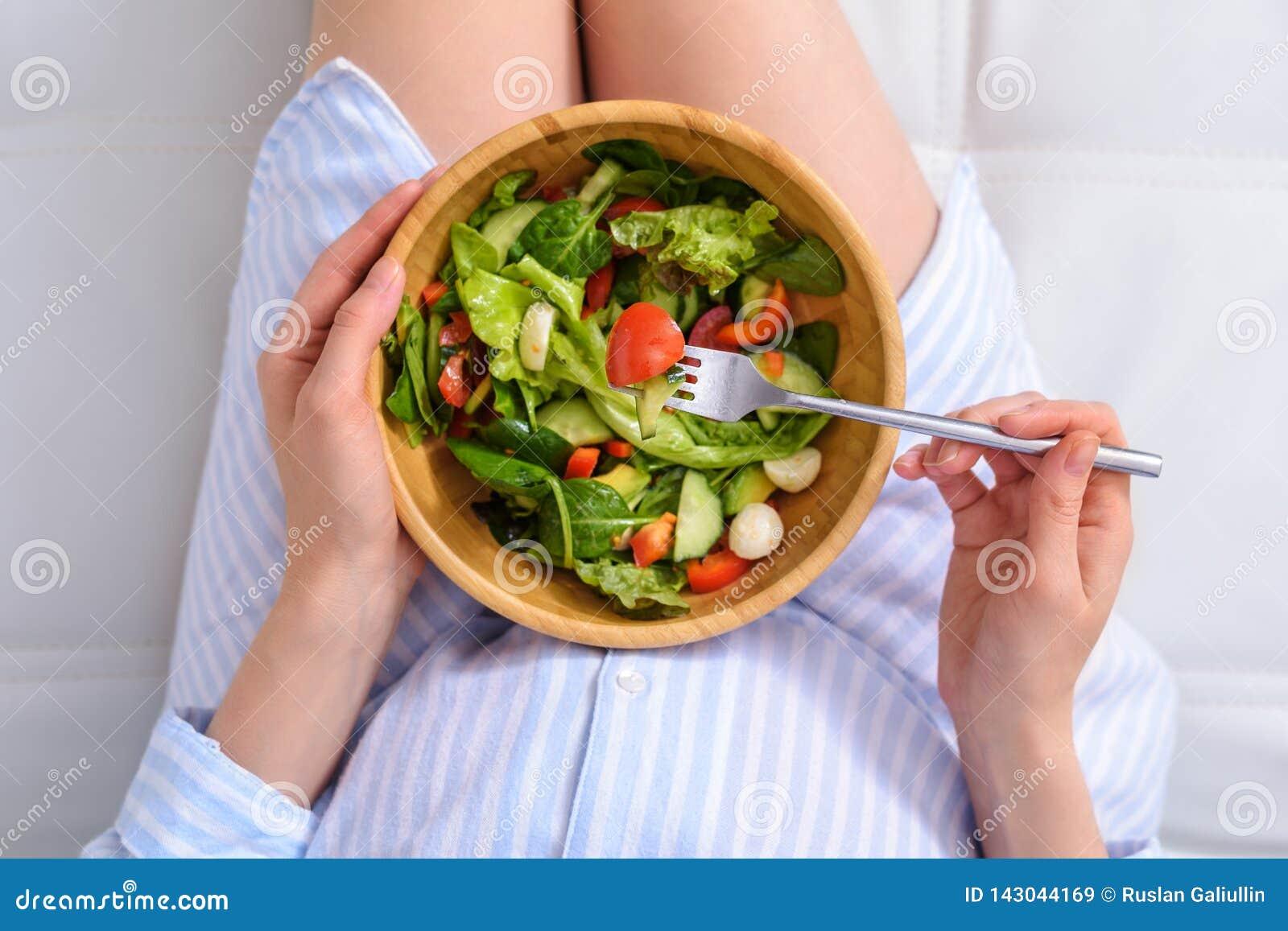 Opinión superior la mujer embarazada que come la ensalada vegetal en cama