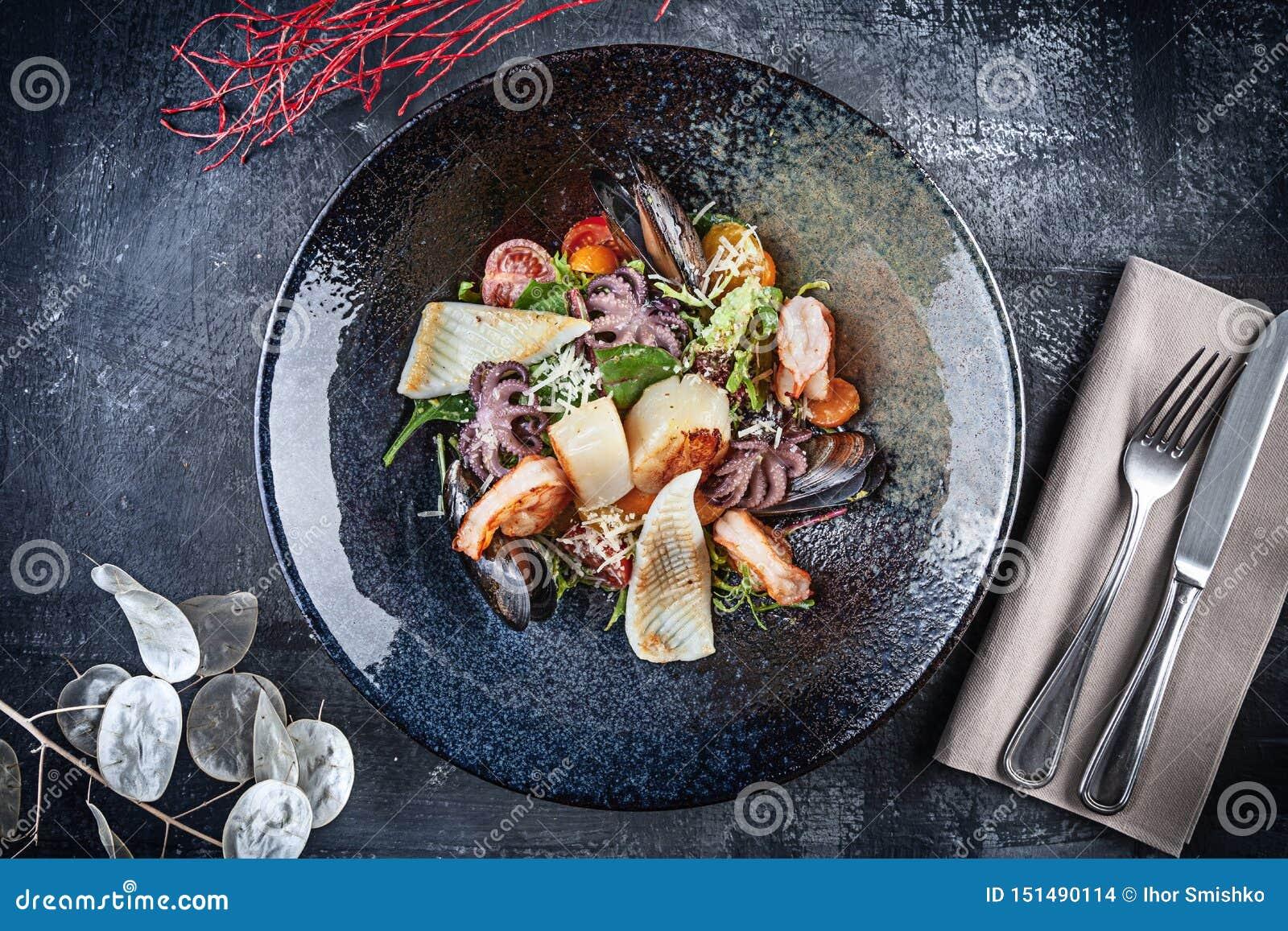Opinión superior sobre la ensalada de los mariscos con el calamar, el camarón, las conchas de peregrino, los mejillones, el pulpo