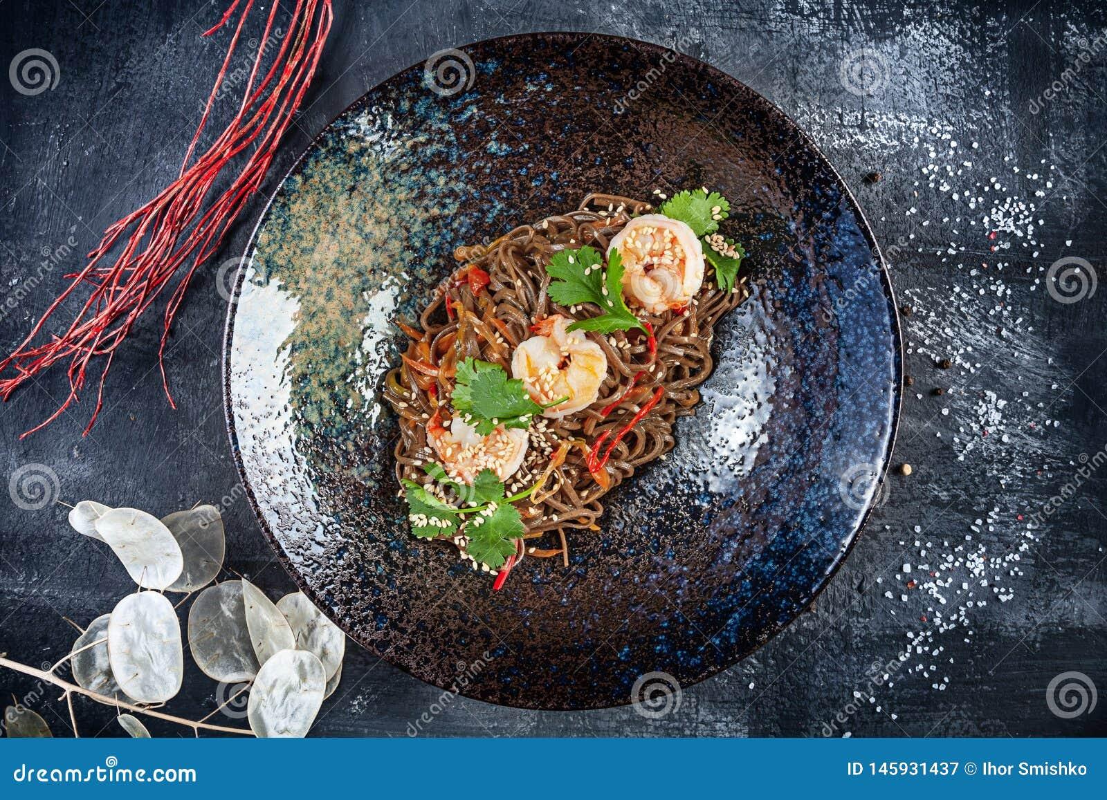 Opinión superior sobre los tallarines tailandeses del alforfón con los camarones servidos en placa texturizada negra en fondo osc
