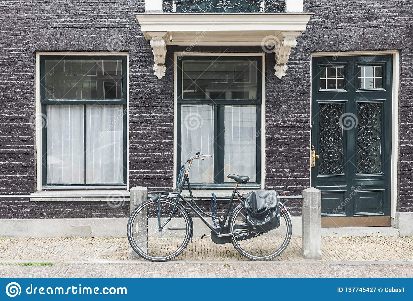 Opinión típica de la calle de Amsterdam en Países Bajos con las puertas y las ventanas y la bicicleta viejas del vintage