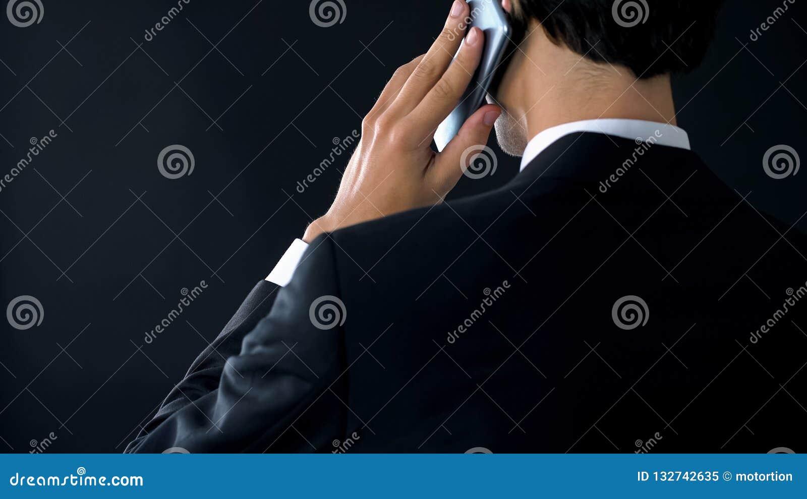 Opinión trasera del teléfono del director de empresa que habla confiado, designando la reunión del socio