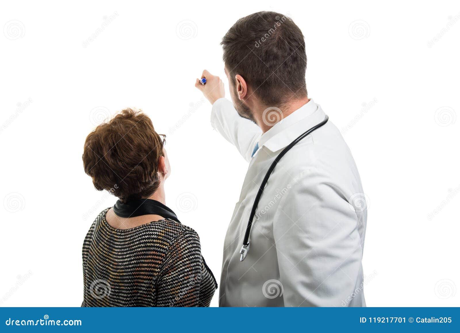 Opinión trasera el doctor de sexo masculino que señala al paciente femenino con el marcador