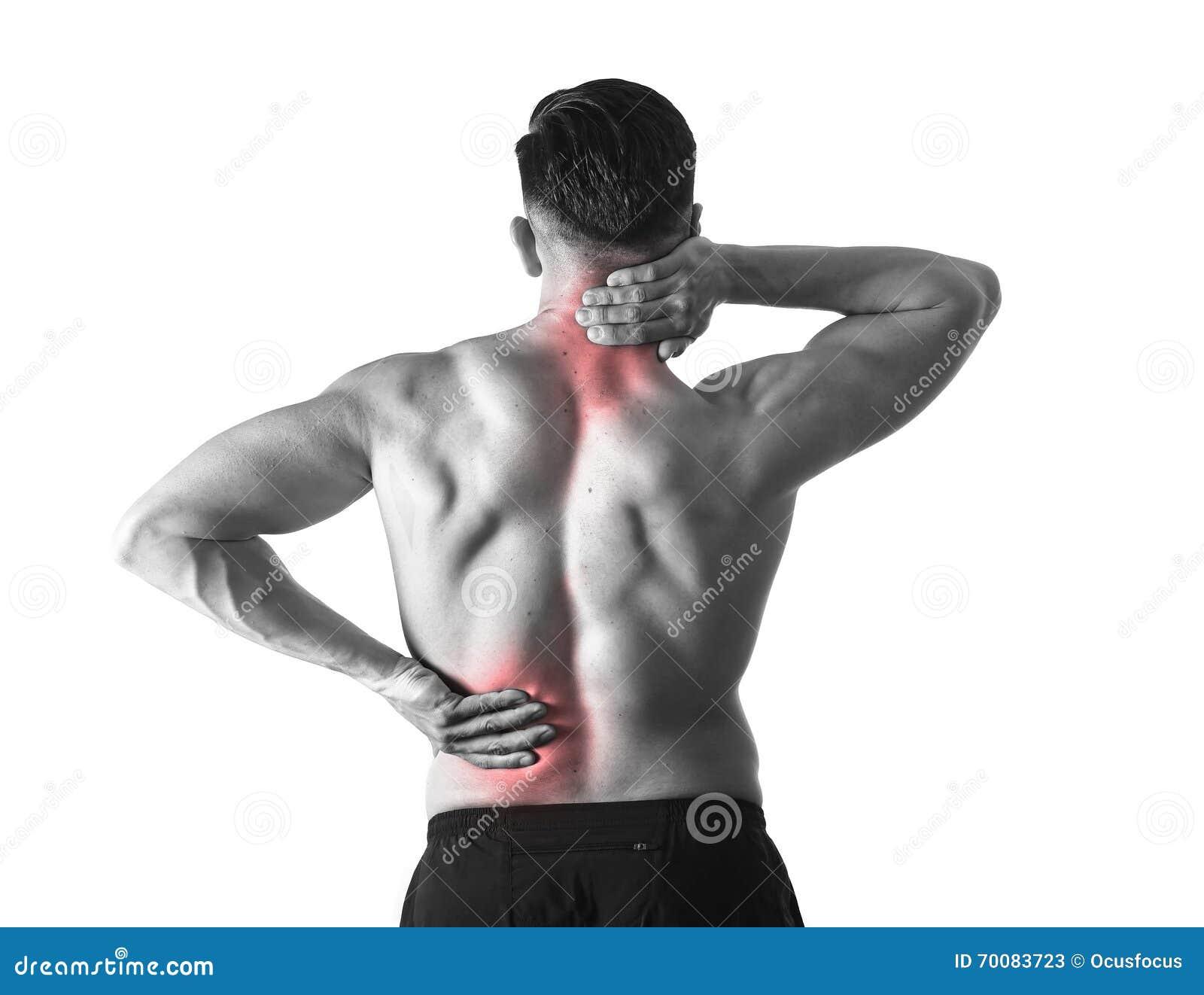 Opinión trasera el hombre joven con el cuerpo muscular que lleva a cabo su dolor espinal del cuello y del sufrimiento de espalda