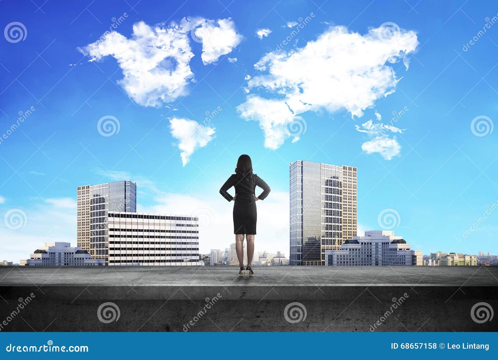 Opinión trasera la mujer de negocios que mira la nube de la forma del mundo