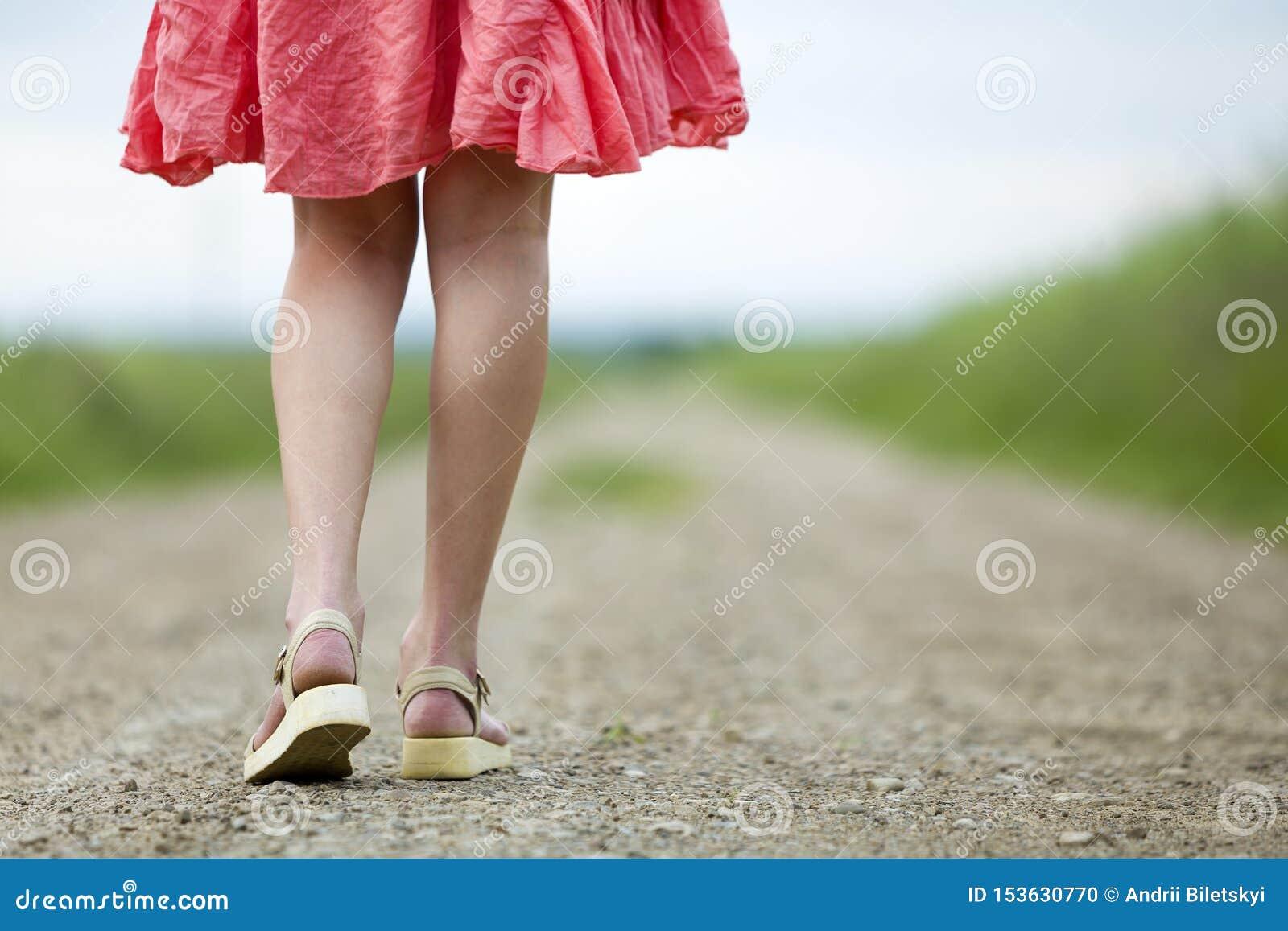 Opinión trasera la mujer joven en piernas rojas del vestido que camina por el camino de tierra el día de verano en fondo soleado