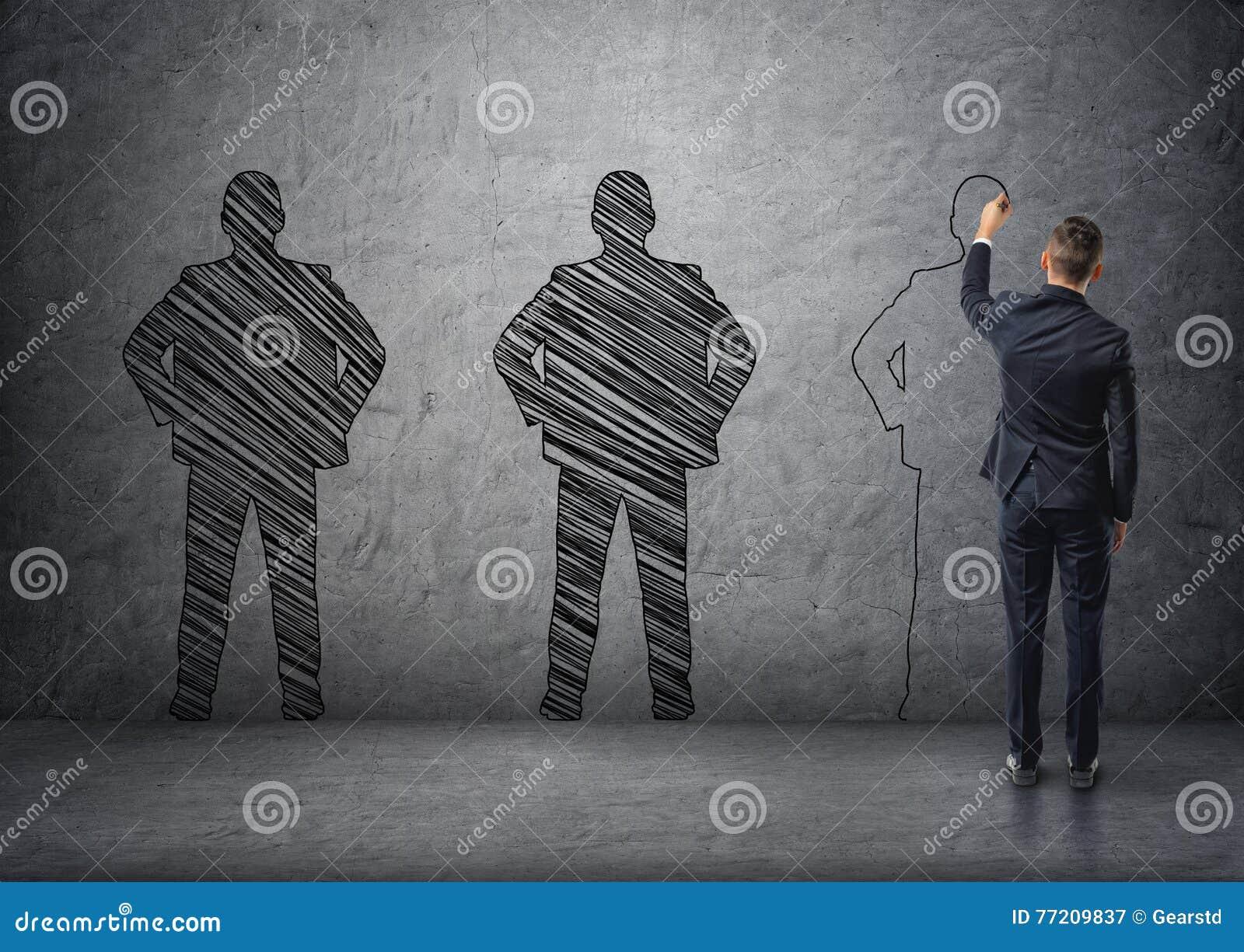 Opinión trasera un hombre de negocios que dibuja el men& oscuro x27; siluetas de s en el muro de cemento