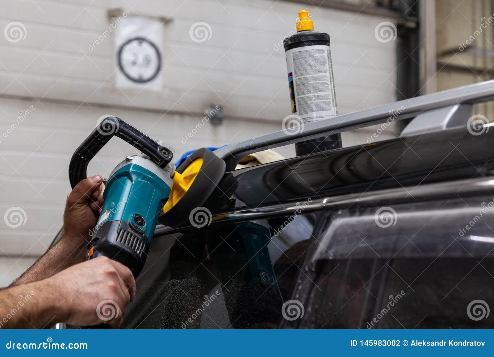 Opini?n del primer sobre las manos de un trabajador del hombre que sostiene un pulidor de la herramienta para pulir el tejado de