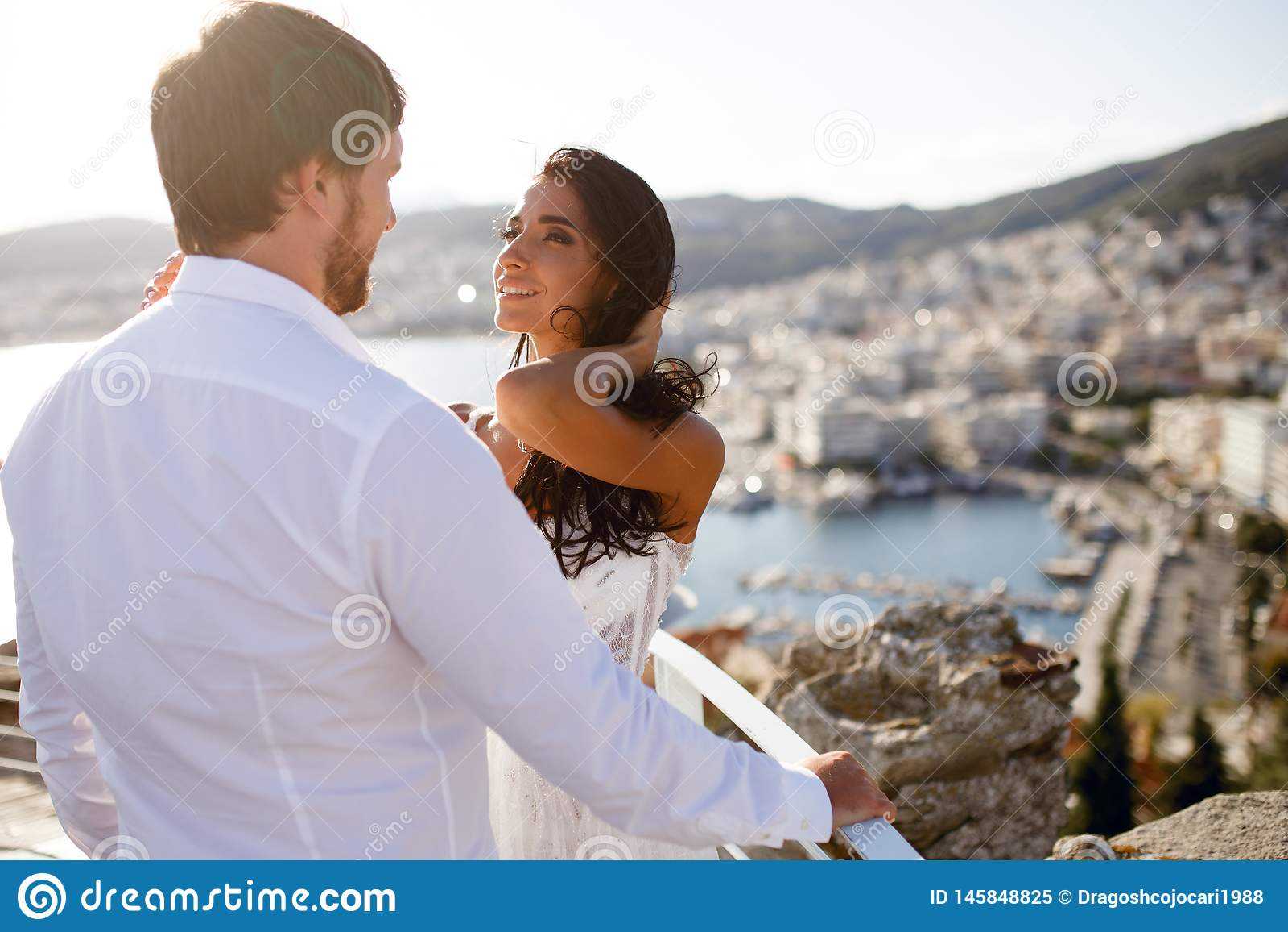 Opini?n trasera una pareja de matrimonios justa hermosa, llevando en la ropa blanca, con el panorama trasero de la ciudad, boda e