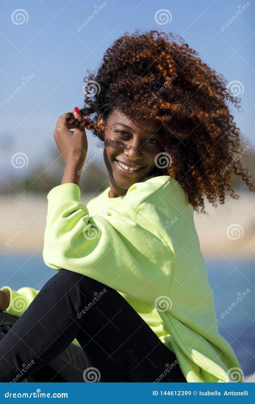 Opini?o lateral uma mulher afro encaracolado bonita que senta-se nas rochas do quebra-mar que riem ao olhar a c?mera fora