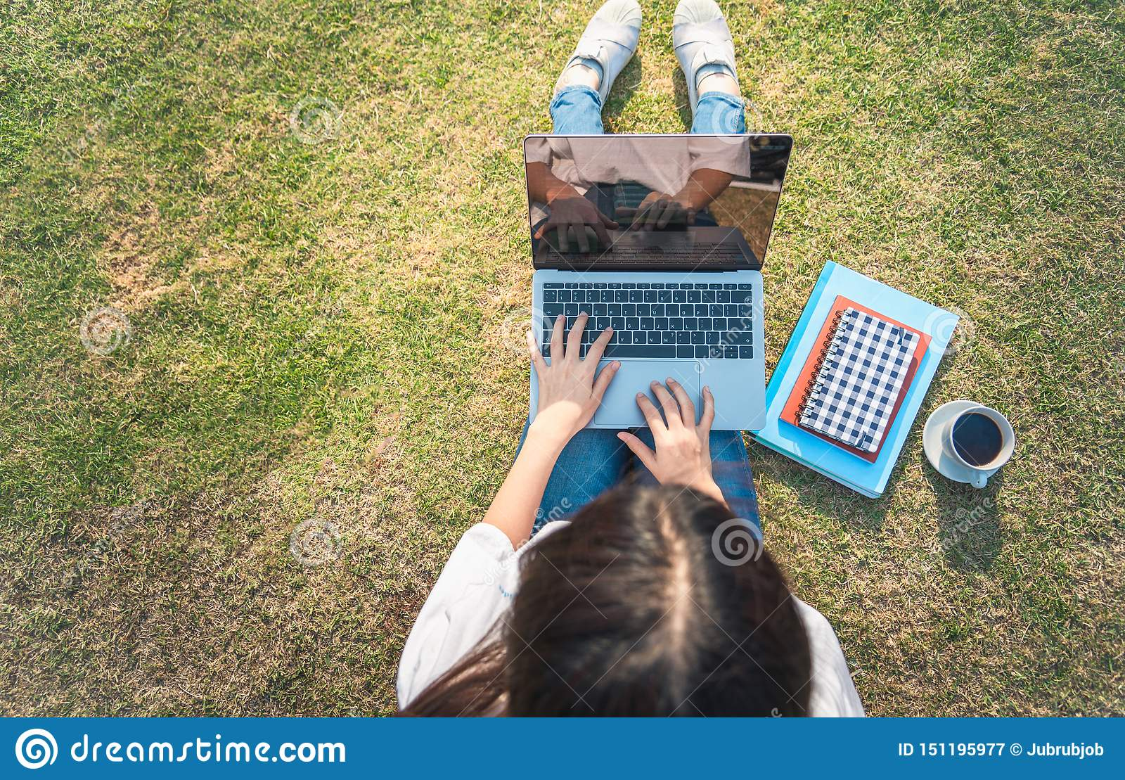 Opini?o superior a jovem mulher no equipamento ocasional usando o port?til ao sentar-se na grama com tabuleta, o caderno e o smar