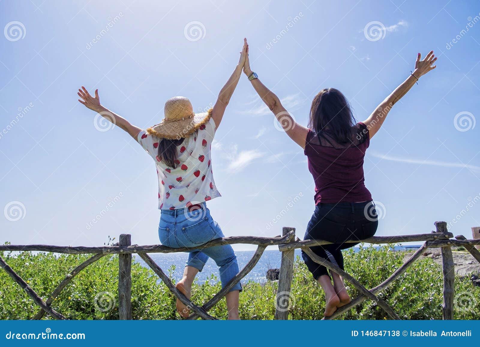Opini?o traseira a jovem mulher dois que senta-se em uma cerca com os bra?os aumentados contra o c?u azul