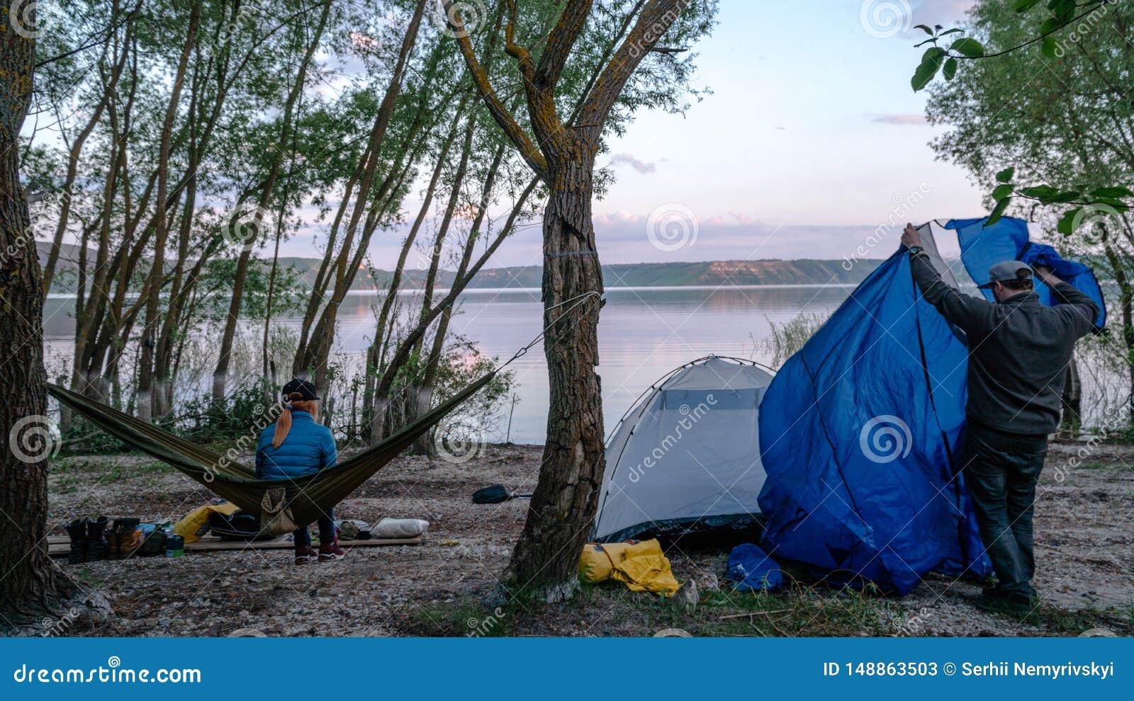 Opini?o traseira a menina que relaxa em uma rede verde-oliva entre duas ?rvores que apreciam a vista no lago na noite do ver?o gr