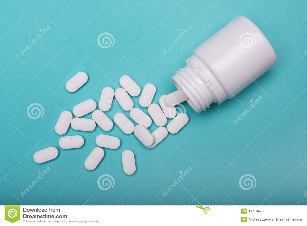 Opioid epidemic. Medication bottle and white pills spilled on blue pastel coloured background. Medication and prescription pills.