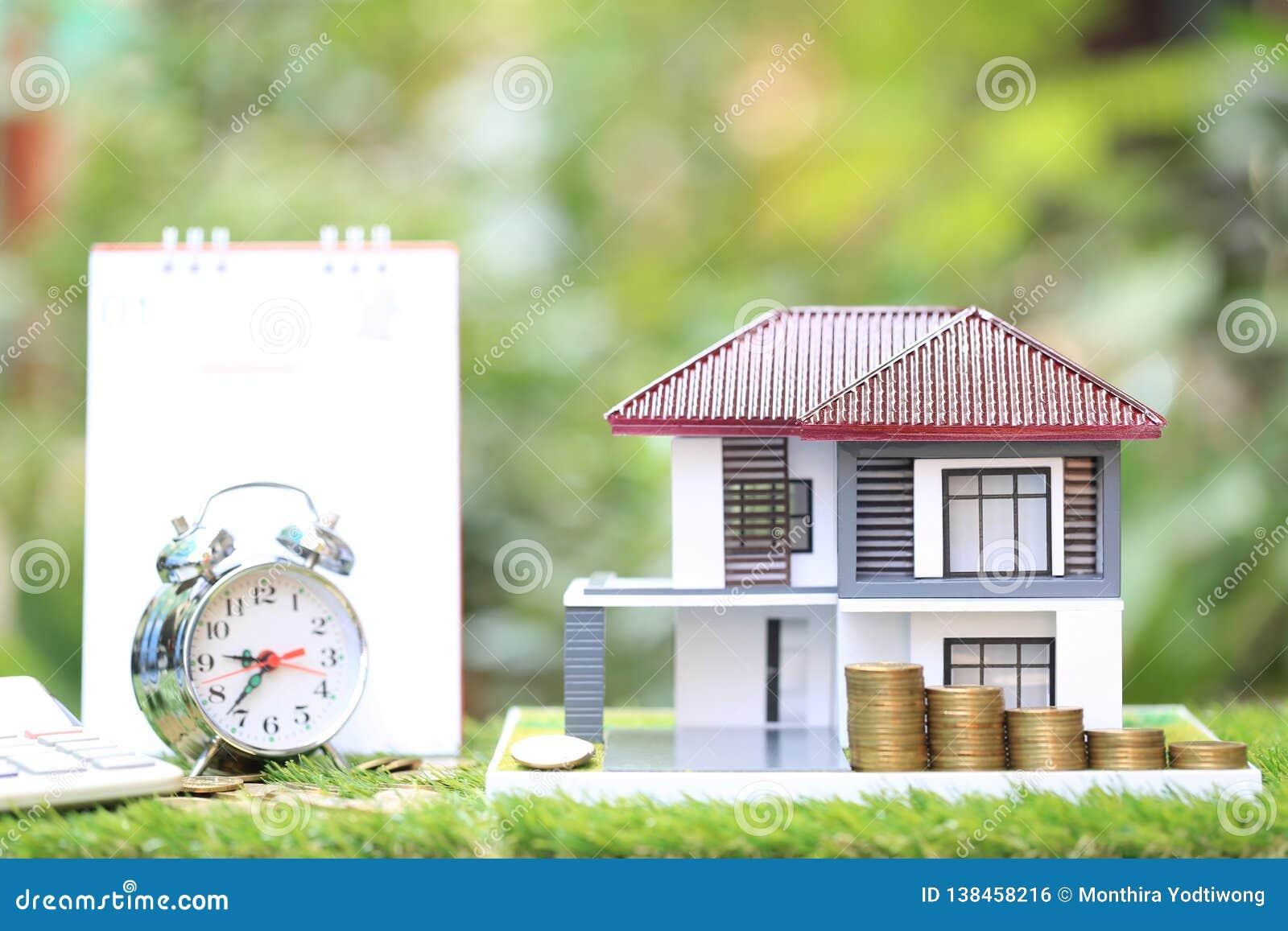 Opodatkowywa czasu pojęcie, modela dom z sztaplowanie monetami pieniądze, budzik i kalendarz na naturalnym zielonym tle,