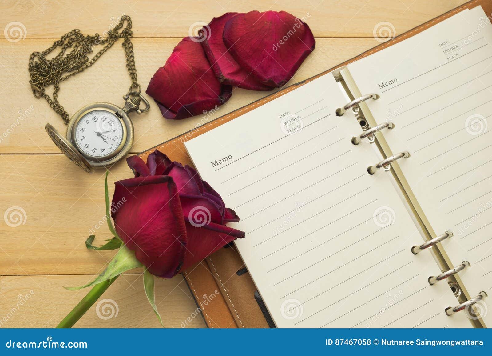 Opróżnia nutową książkę, kieszeniowego zegarek i czerwone róże stawiającą na drewnianym,