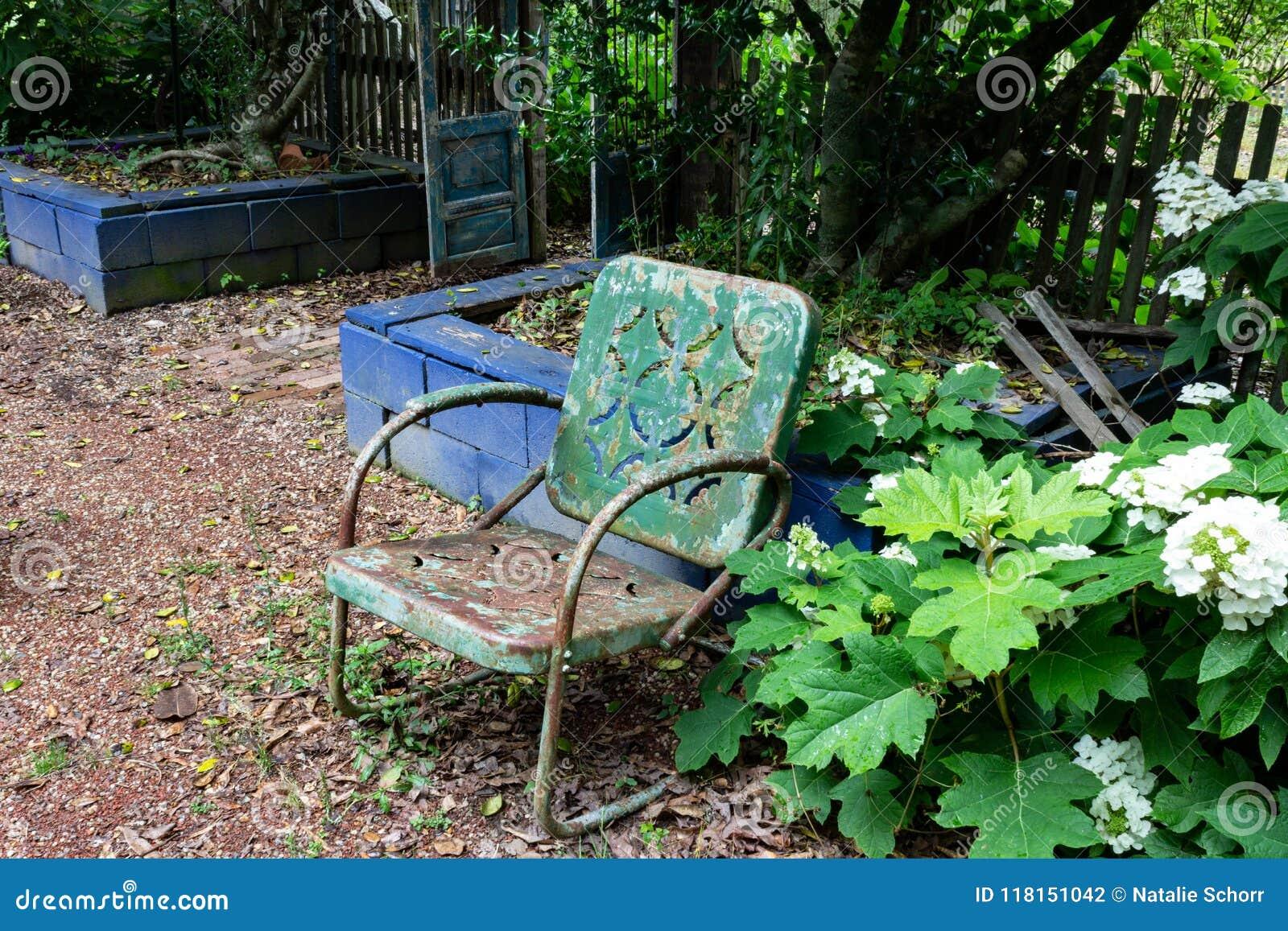 Opróżnia starego zielonego metalu krzesła przeciw błękitnej blok ścianie, starzeje się śmiertelnego żal nieobecności pojęcie