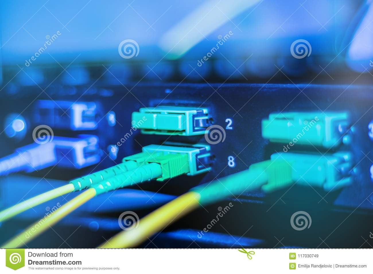 Optical cable in internet network devices. Green and yellow optical fiber cable in switch