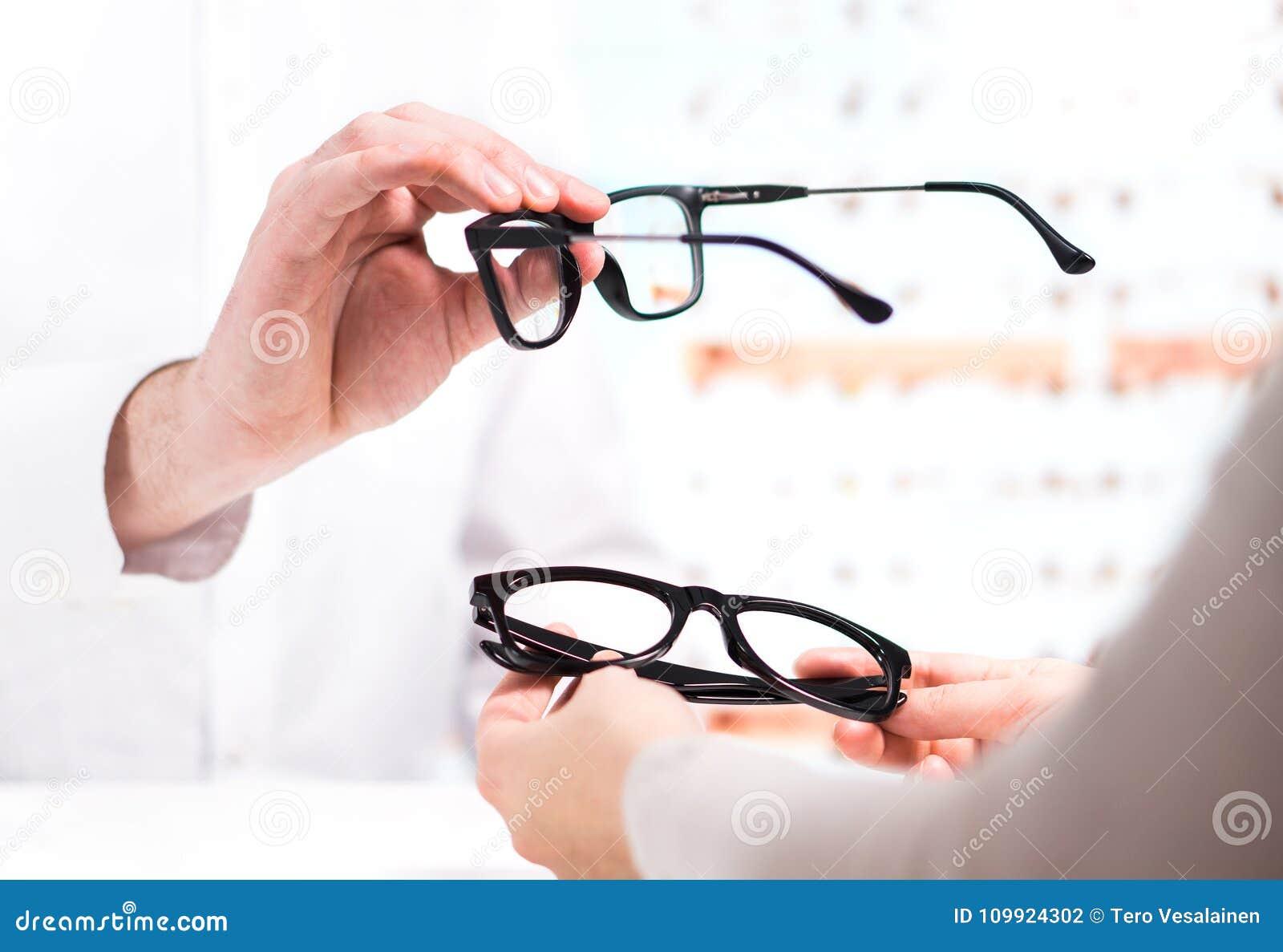 Optician давая новые стекла к клиенту для испытывать и пробовать