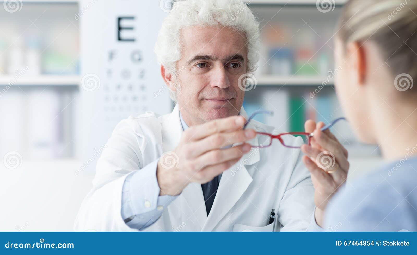 adc24bb0782492 L optométriste masculin donnant de nouveaux verres au patient après la  visite, les soins de santé et l oeil s inquiètent le concept
