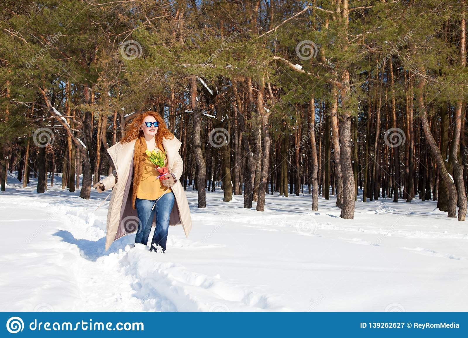 Smiling joyful woman walking through snowdrifts with forest on the background